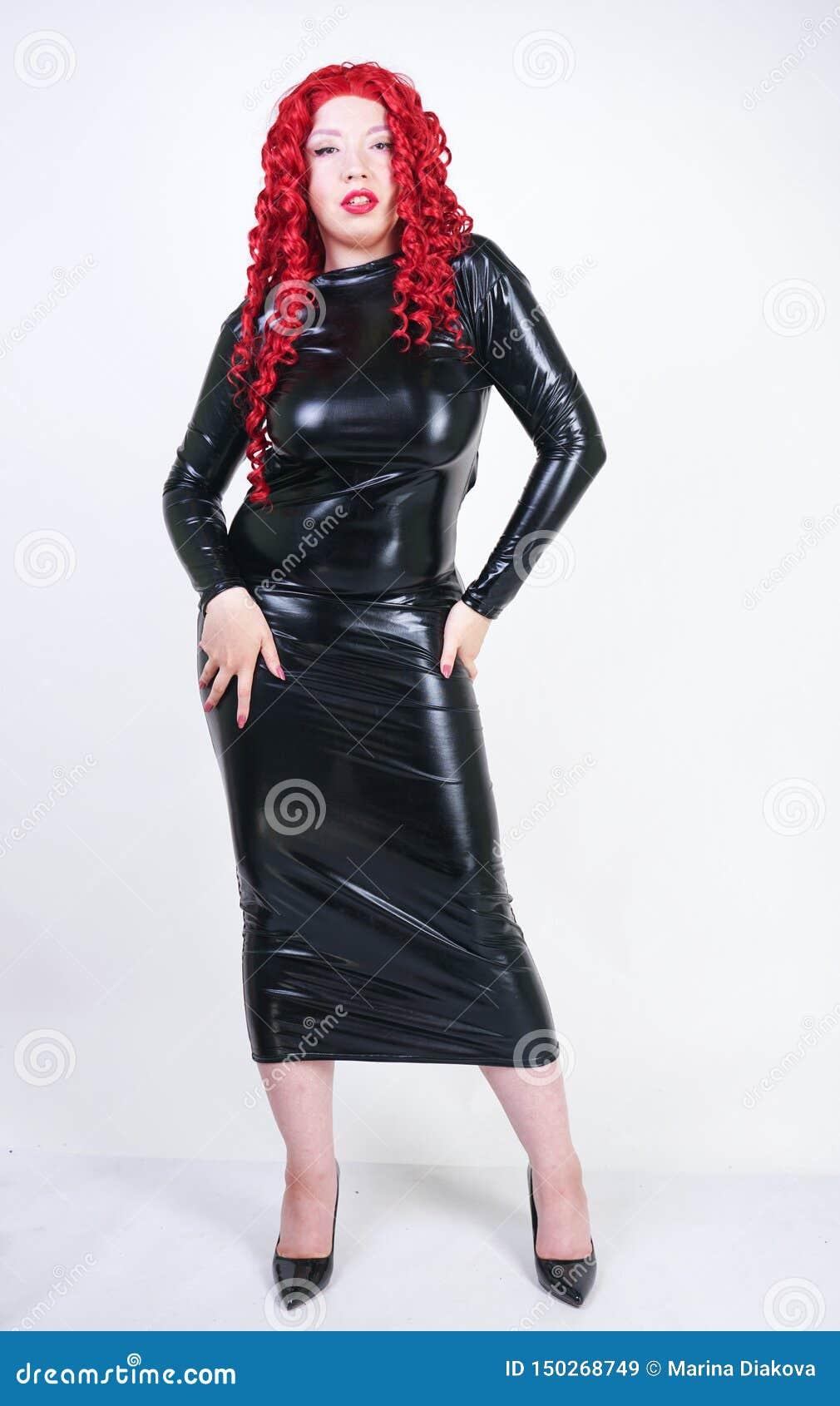 Femme plus luxueuse de taille avec le visage asiatique, le maquillage lumineux et les cheveux bouclés rouges posant dans la longu