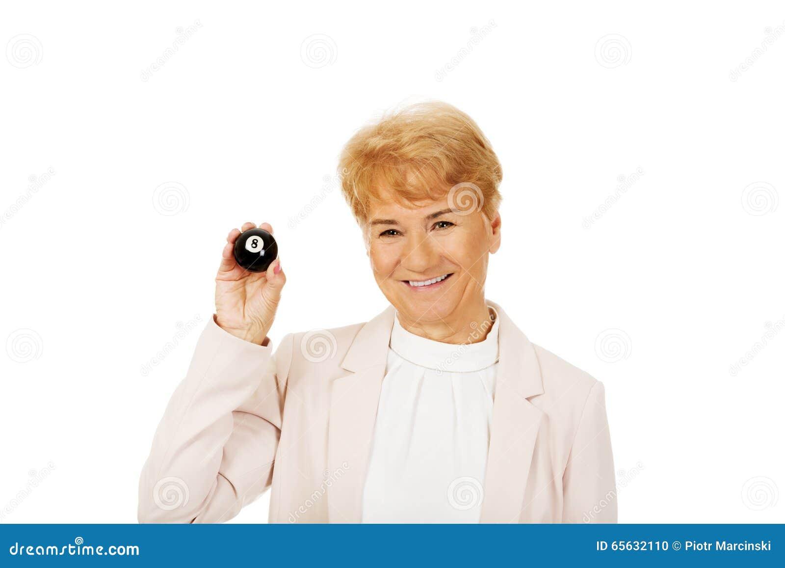 Femme pluse âgé heureuse d affaires tenant la billard-boule huit