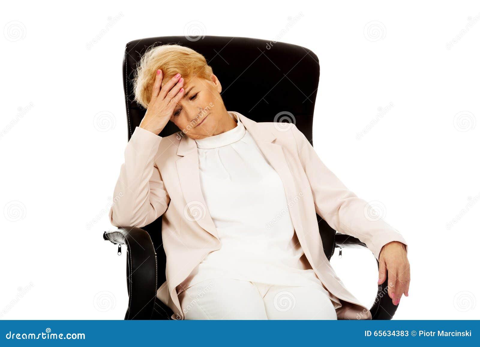 Femme pluse âgé inquiétée d affaires s asseyant sur le fauteuil