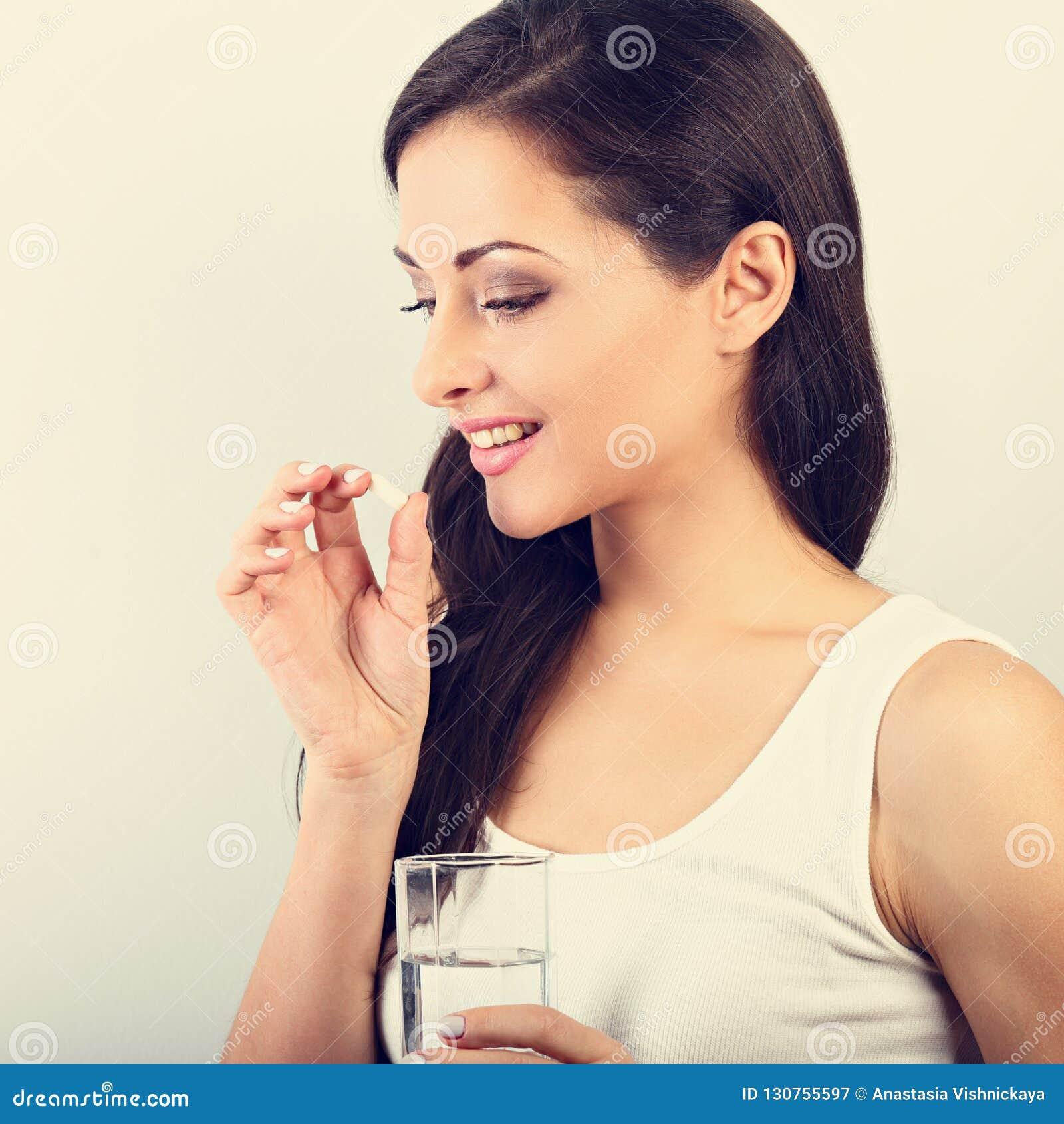 Femme positive de sourire heureuse mangeant la pilule et tenant le gla
