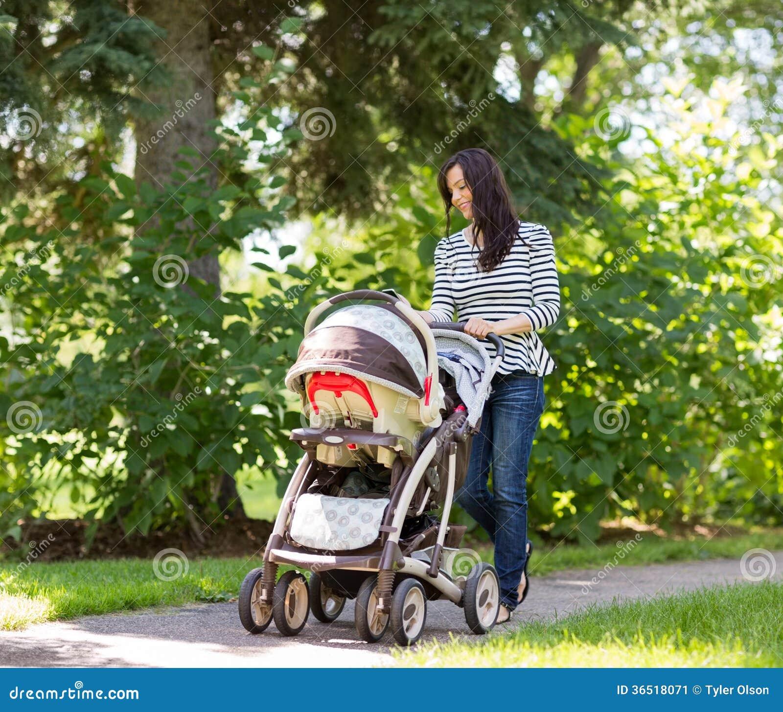 Femme poussant la voiture d enfant en parc