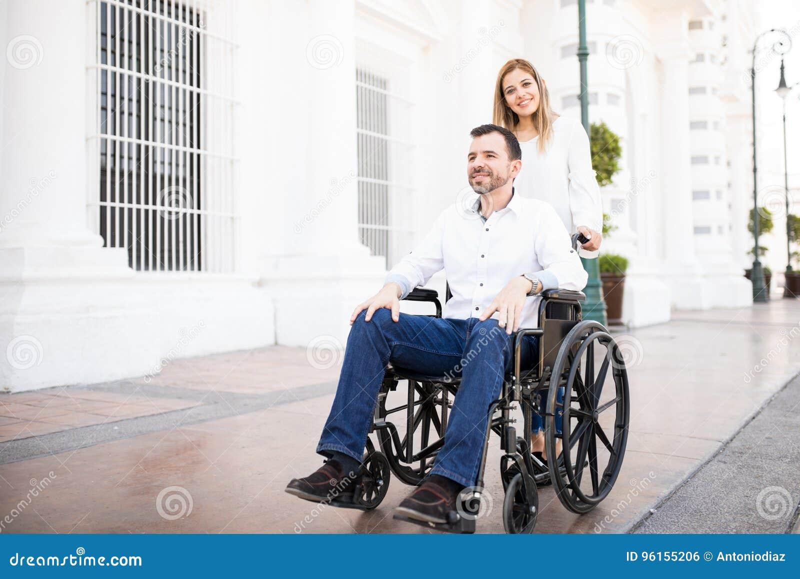 Femme poussant son boyfriend& x27 ; fauteuil roulant de s