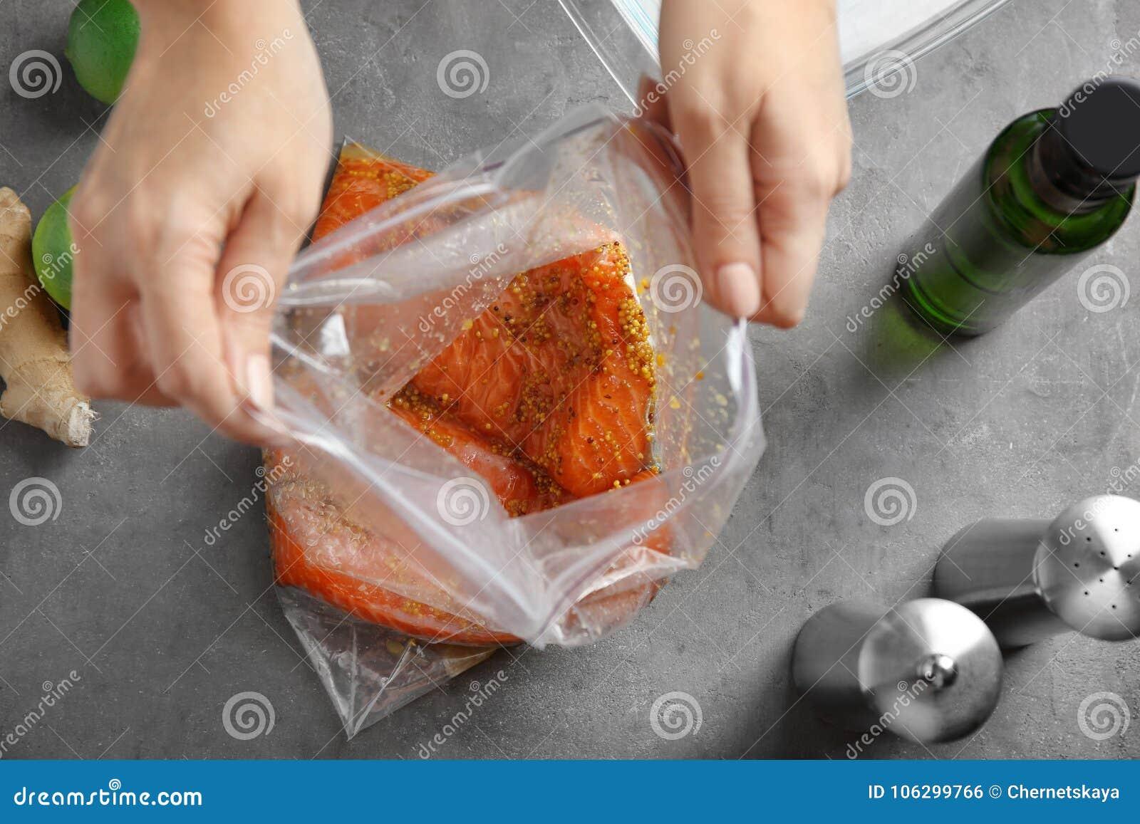 Femme préparant le filet saumoné avec la marinade de moutarde de miel dans le sac de serrure de fermeture éclair