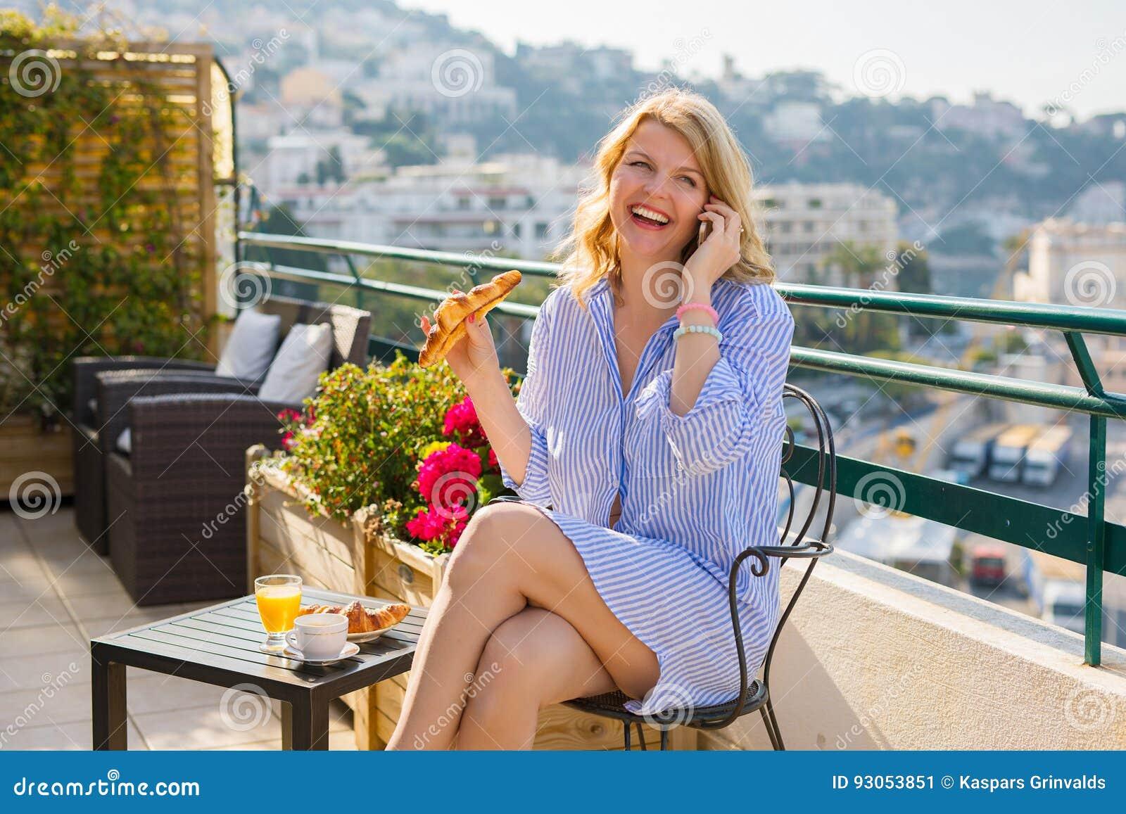 femme prenant le petit d jeuner dehors et parlant du t l phone portable photo stock image. Black Bedroom Furniture Sets. Home Design Ideas