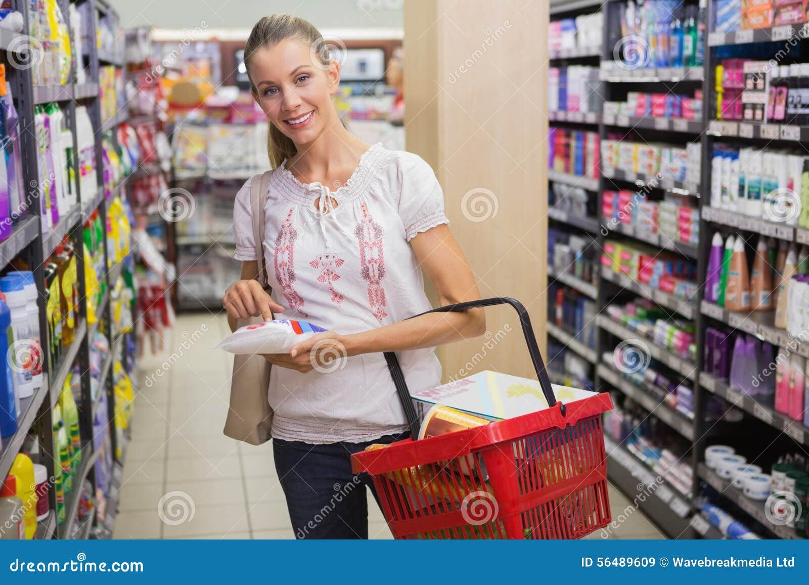 Femme prenant un sac de riz dans l étagère du bas-côté