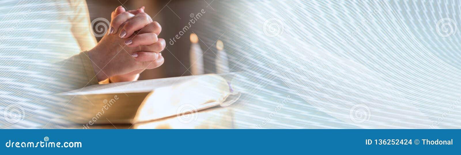Femme priant avec ses mains au-dessus de la bible, lumière dure Drapeau panoramique