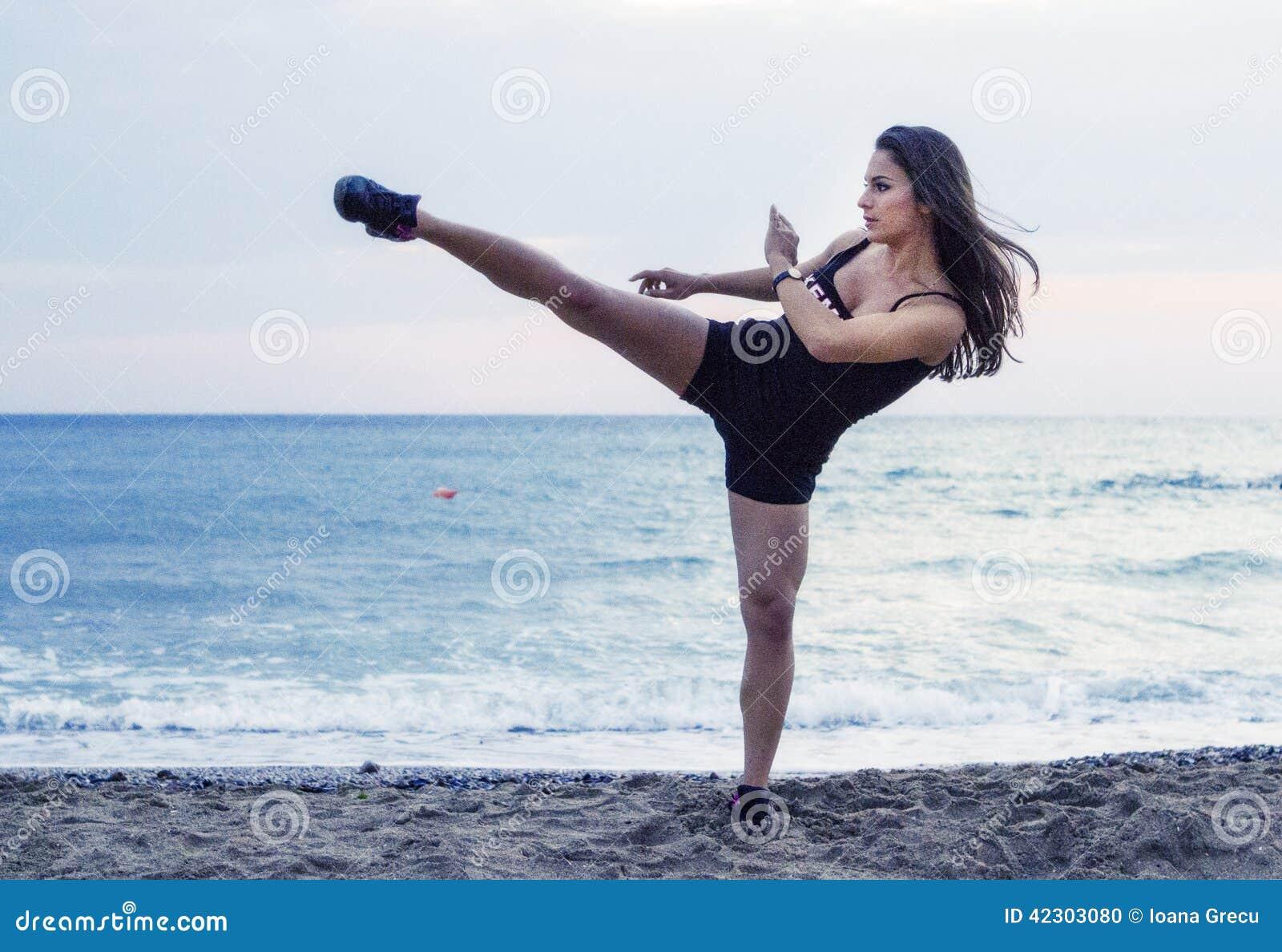 Femme puissante exécutant le coup-de-pied d arts martiaux