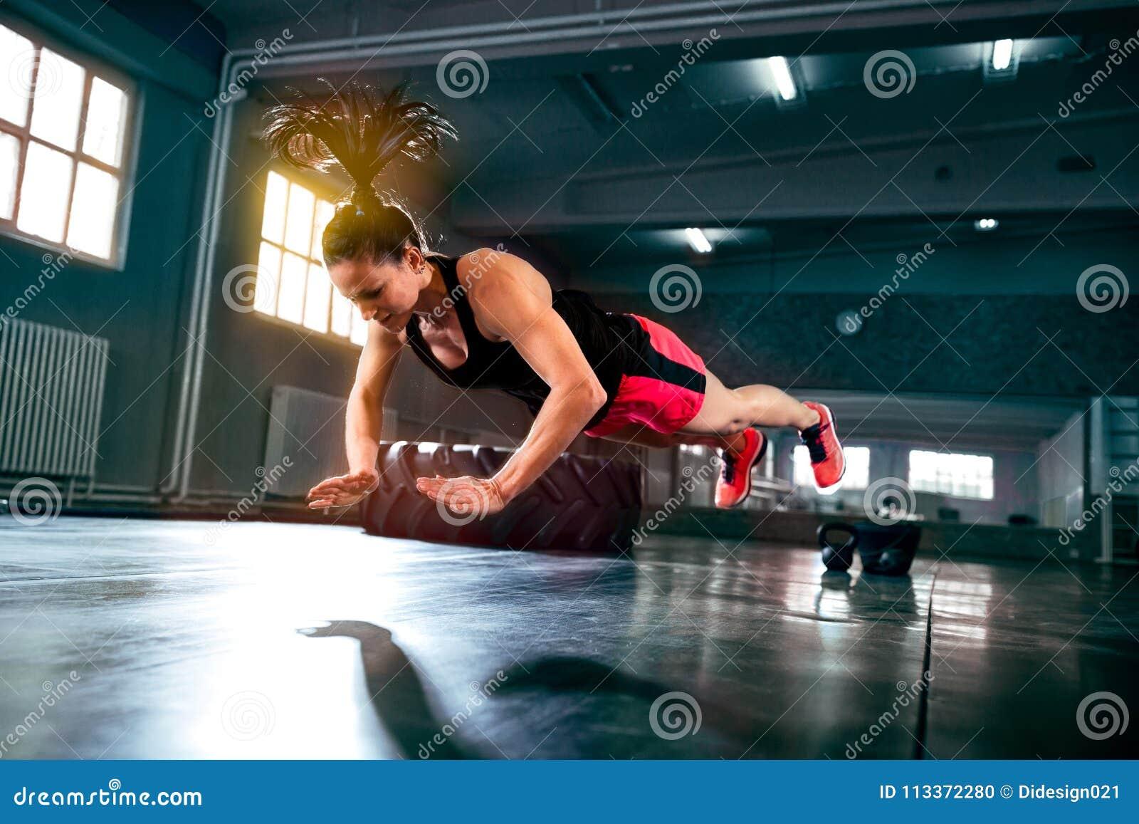 Femme puissante forte faisant la séance d entraînement intense dure au gymnase