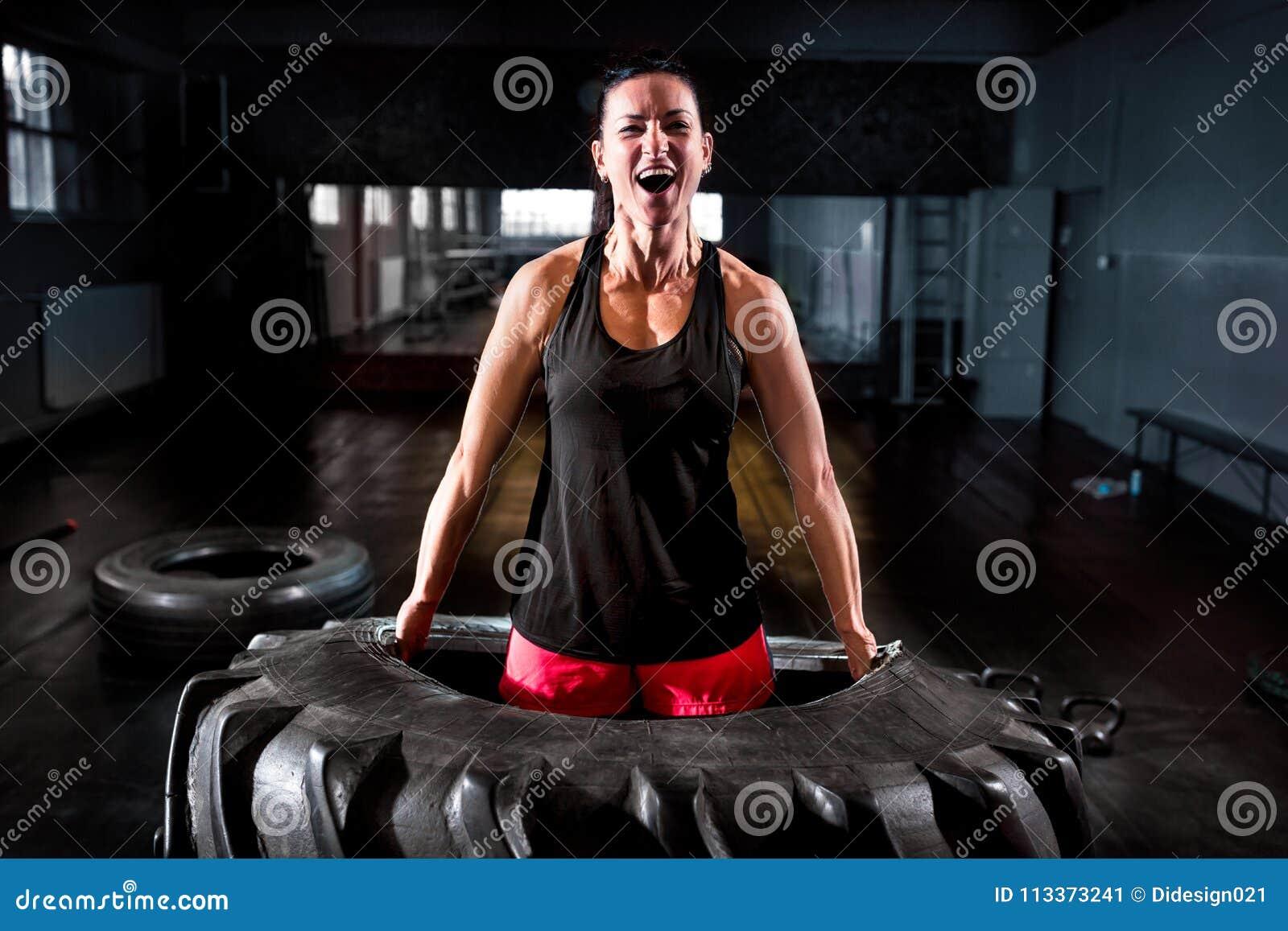 Femme puissante soulevant le grand pneu à la formation intense