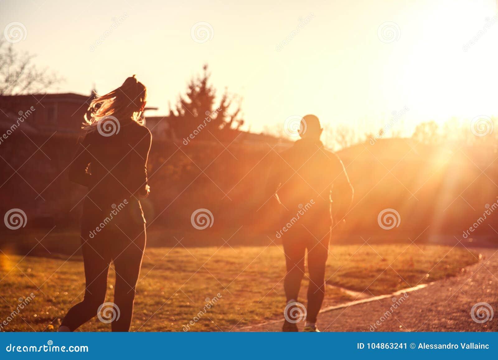 Femme pulsante et homme sportif courant au-dessus du soleil rougeoyant, Spor