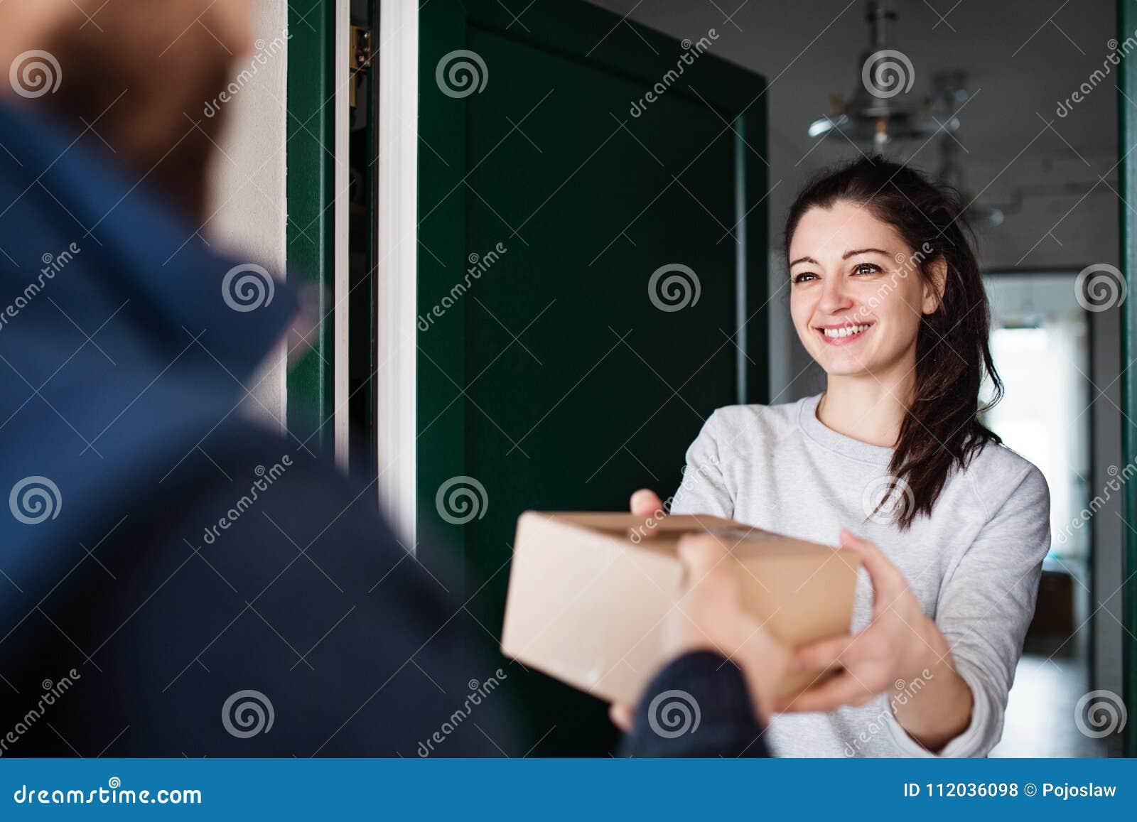 Femme recevant le colis du livreur à la porte