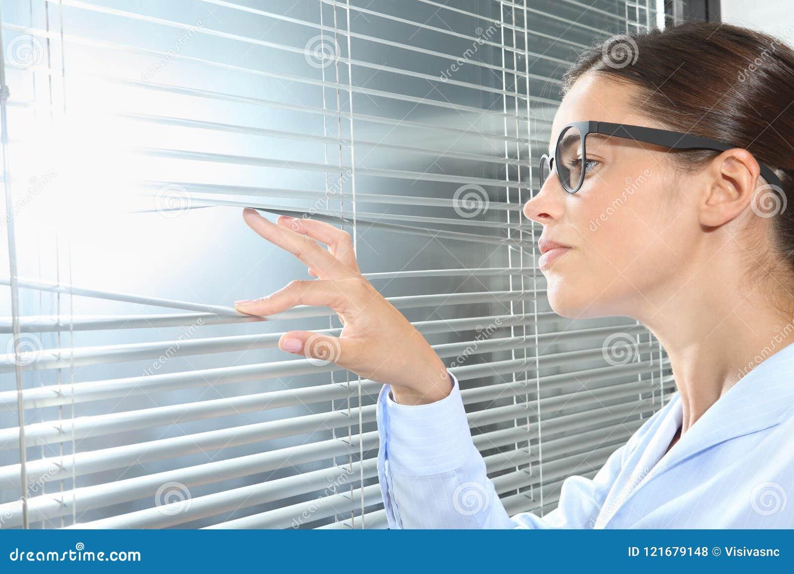 Femme regardant hors de la fenêtre avec des abat-jour