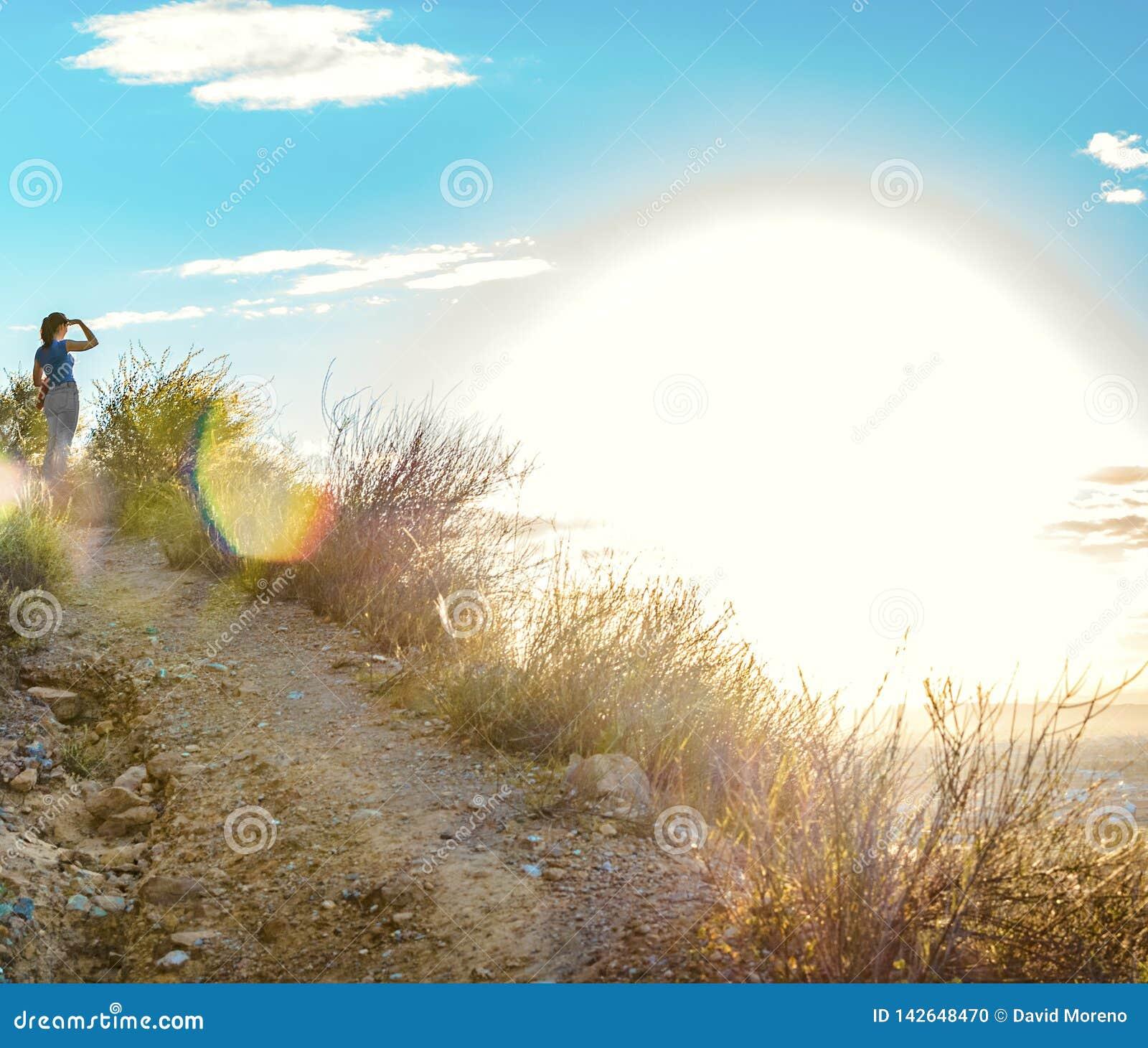 Femme regardant le coucher du soleil du haut d une montagne