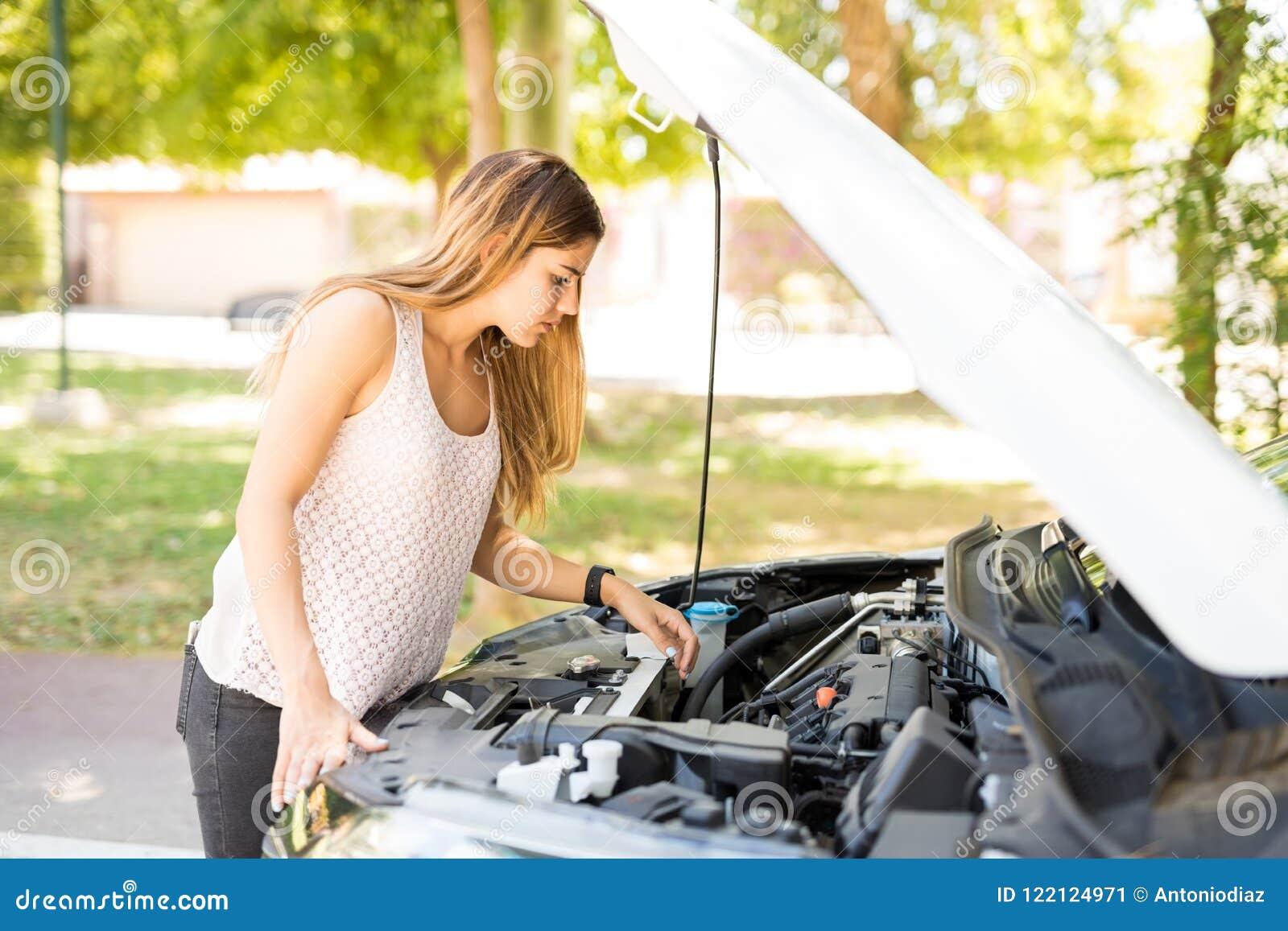 Femme regardant le moteur de sa voiture cassée