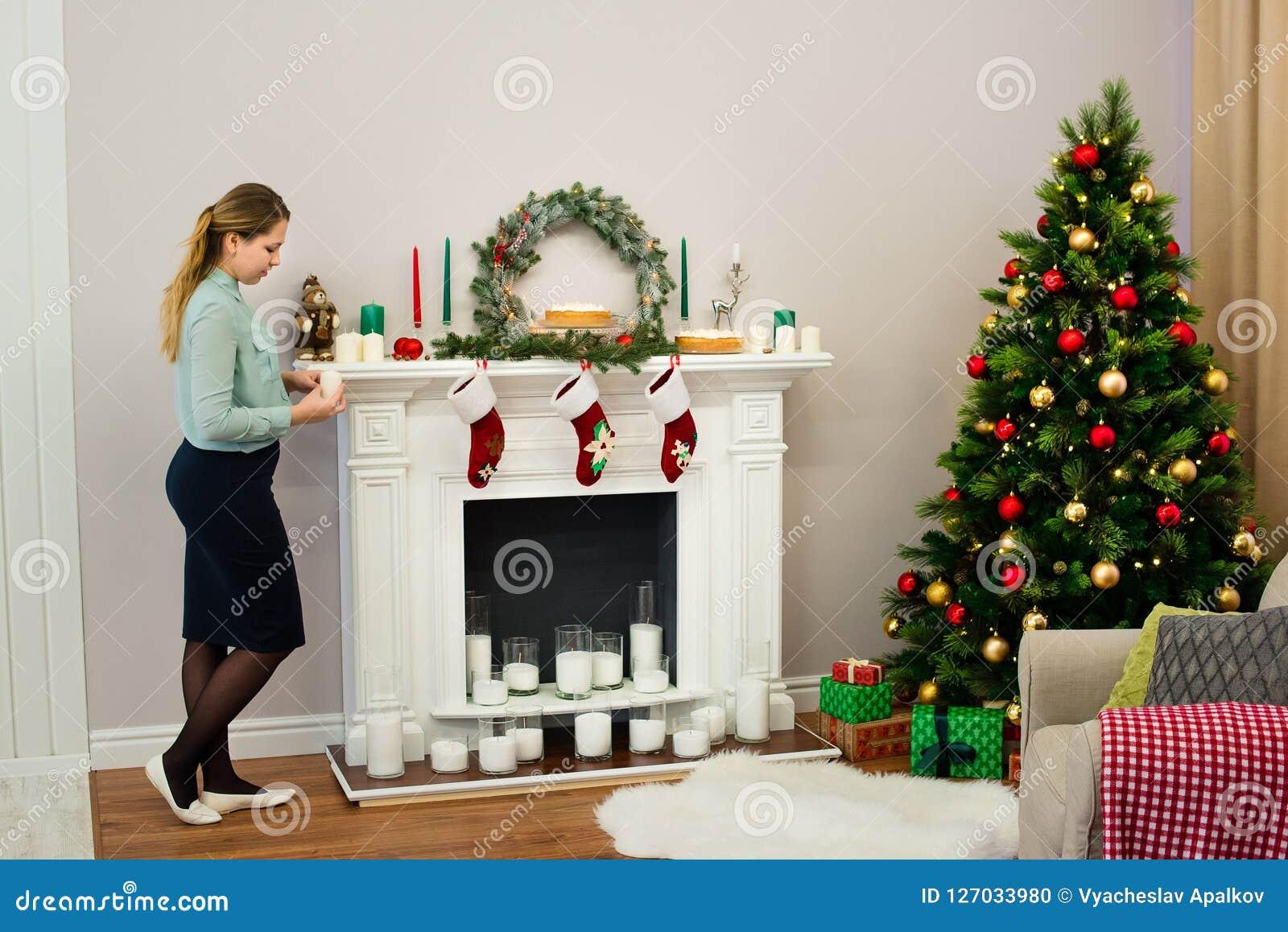 Femme regardant sur une bougie dans des ses mains dans la maison
