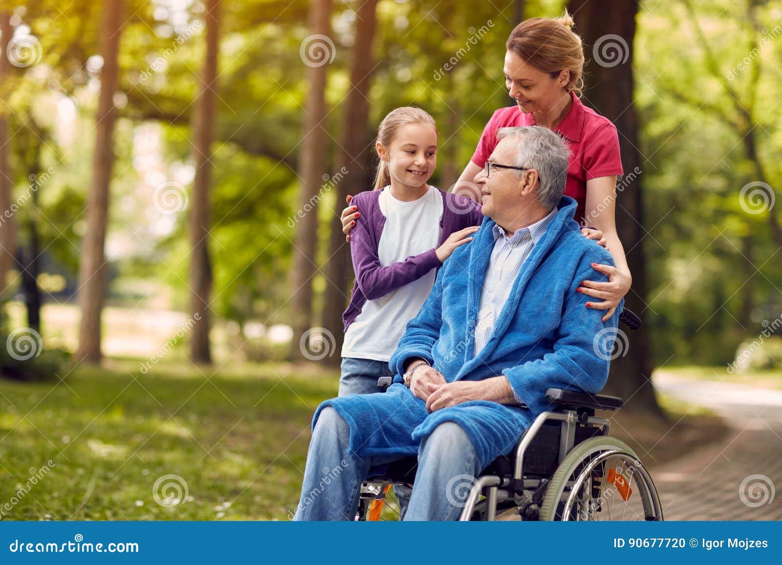 Femme rendant visite à son père handicapé dans le fauteuil roulant avec le granddaugh