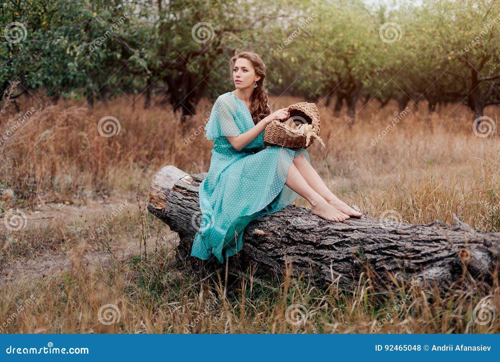 Femme romantique portant la longue robe élégante se reposant sur le champ, saison d automne, relaxation dans la campagne, appréci