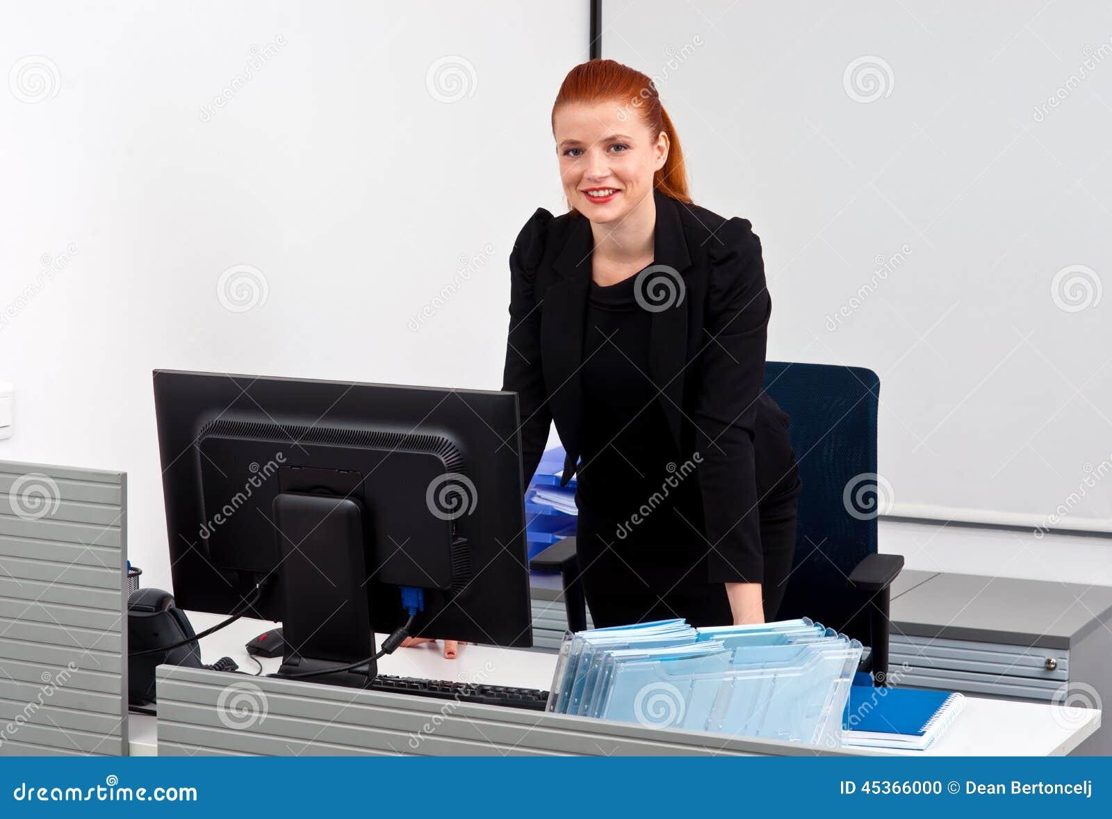 Femme rouge d affaires de cheveux dans le bureau