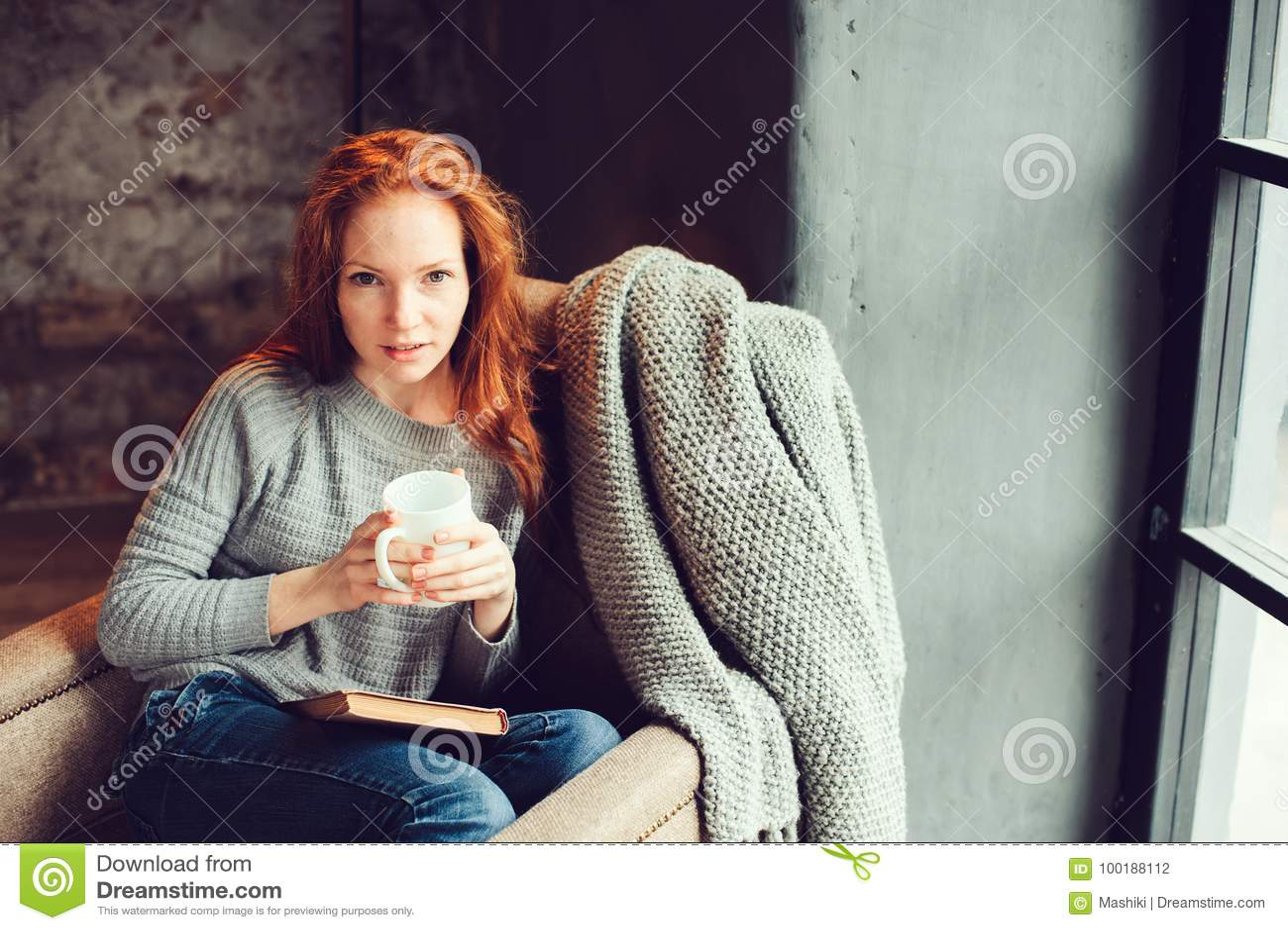 Femme rousse heureuse détendant à la maison dans le week-end confortable d hiver ou d automne avec le livre et la tasse de thé ch