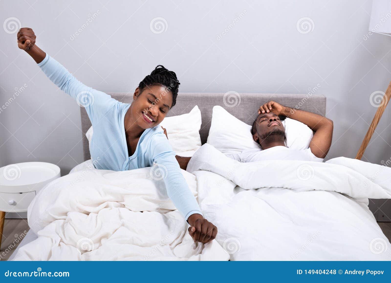 Femme s ?tirant tandis que son mari se trouvant sur le lit