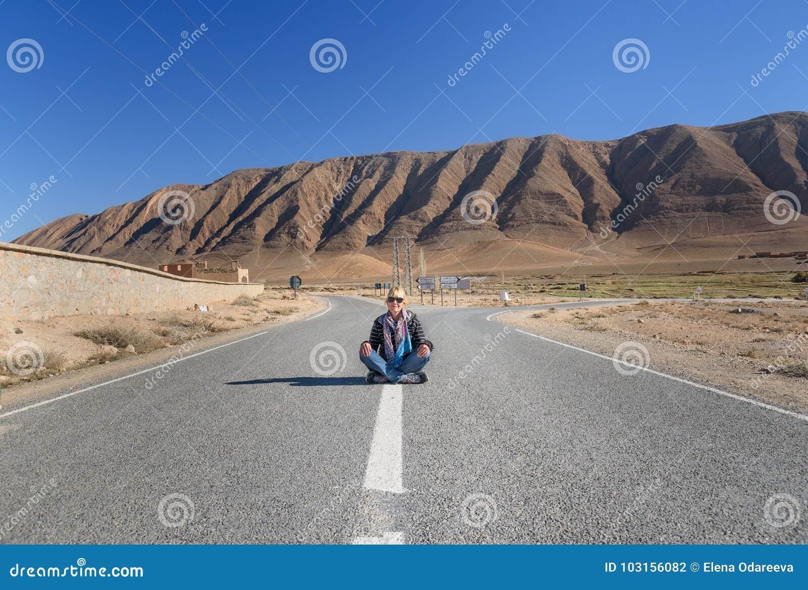 Femme s asseyant avec la jambe croisée sur la route Fourchette dans la route morocco