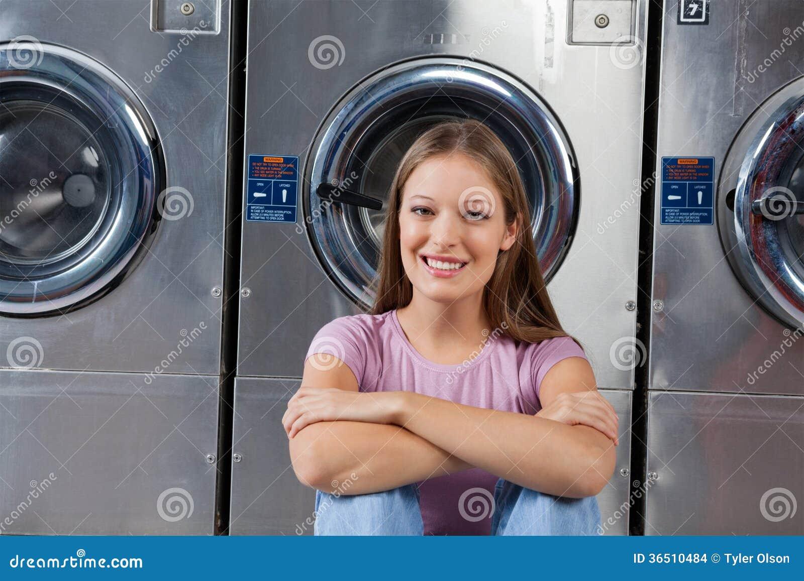 Femme s asseyant contre des machines à laver dans la blanchisserie