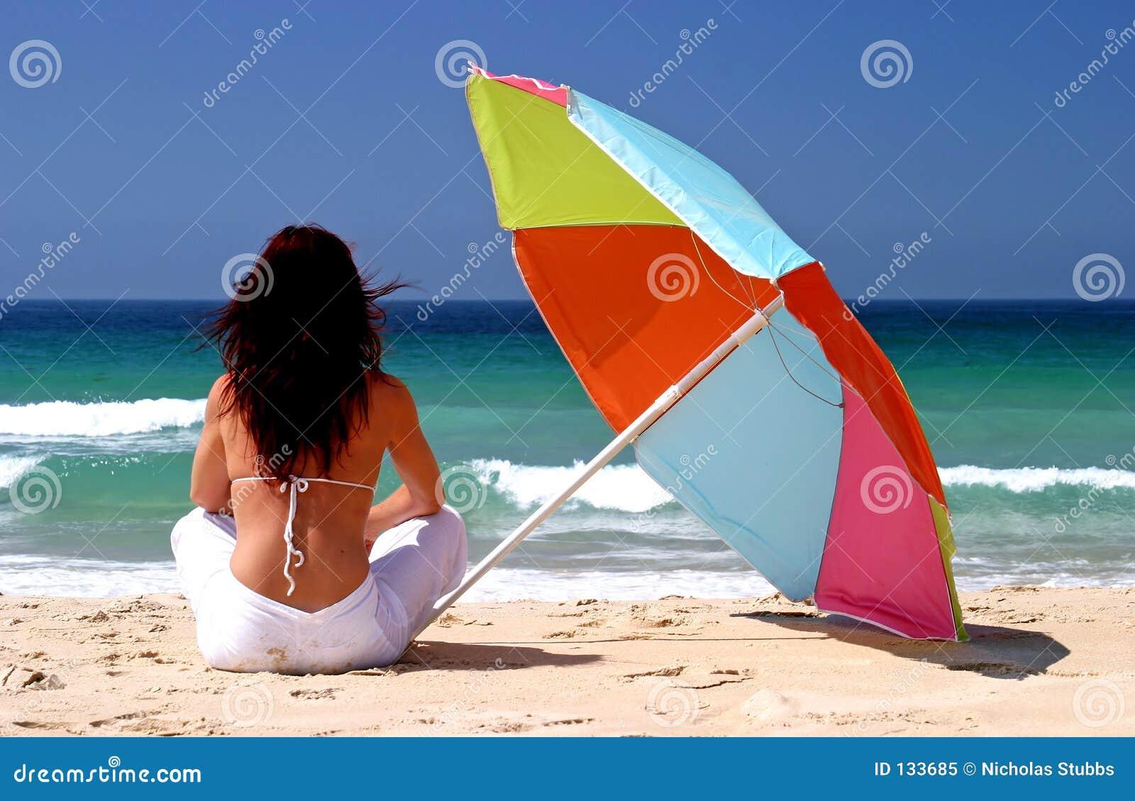Femme s asseyant sous le parasol coloré sur la plage sablonneuse blanche