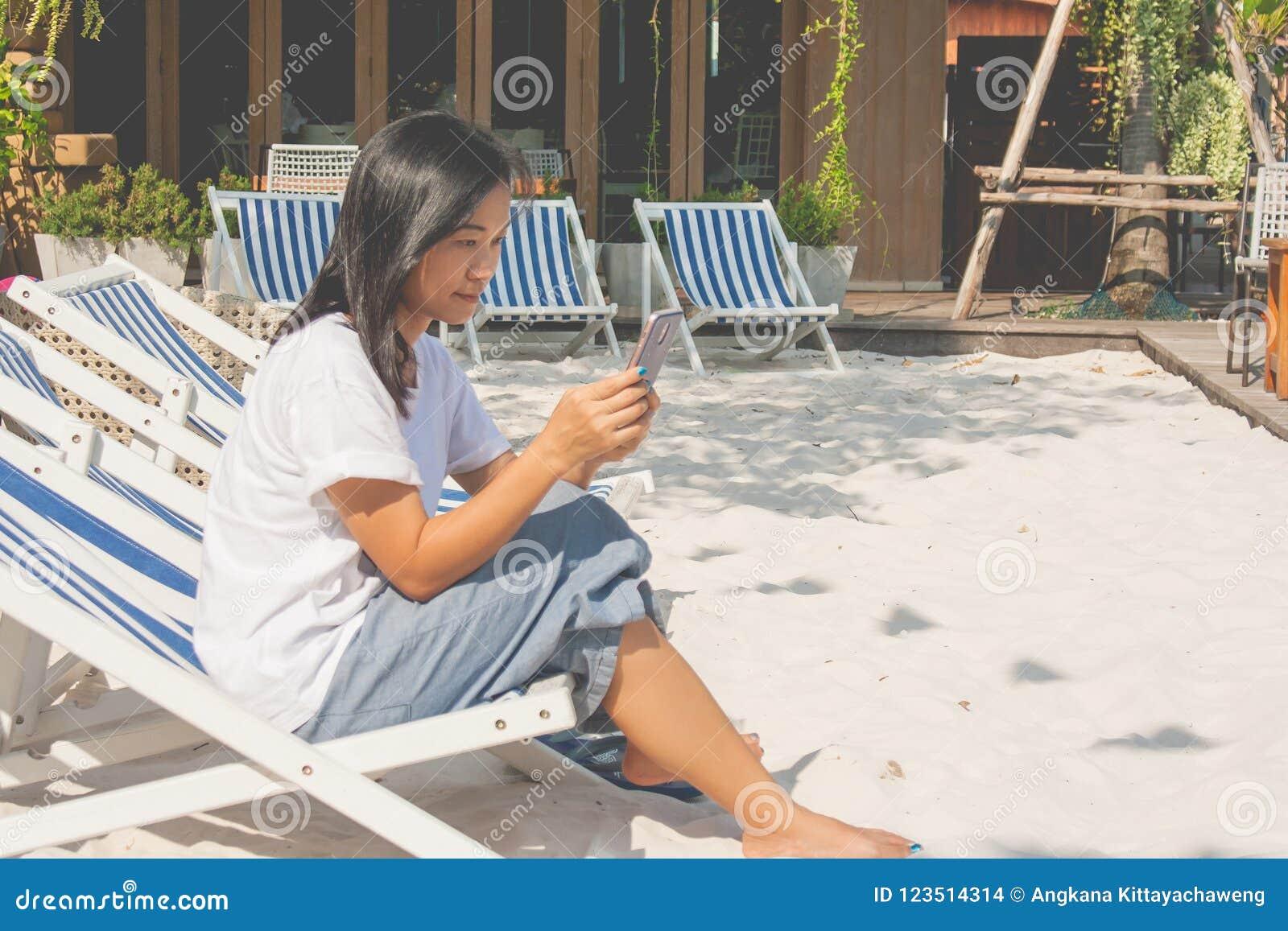 Femme s asseyant sur la chaise de plage et jouant le smartphone à l extérieur