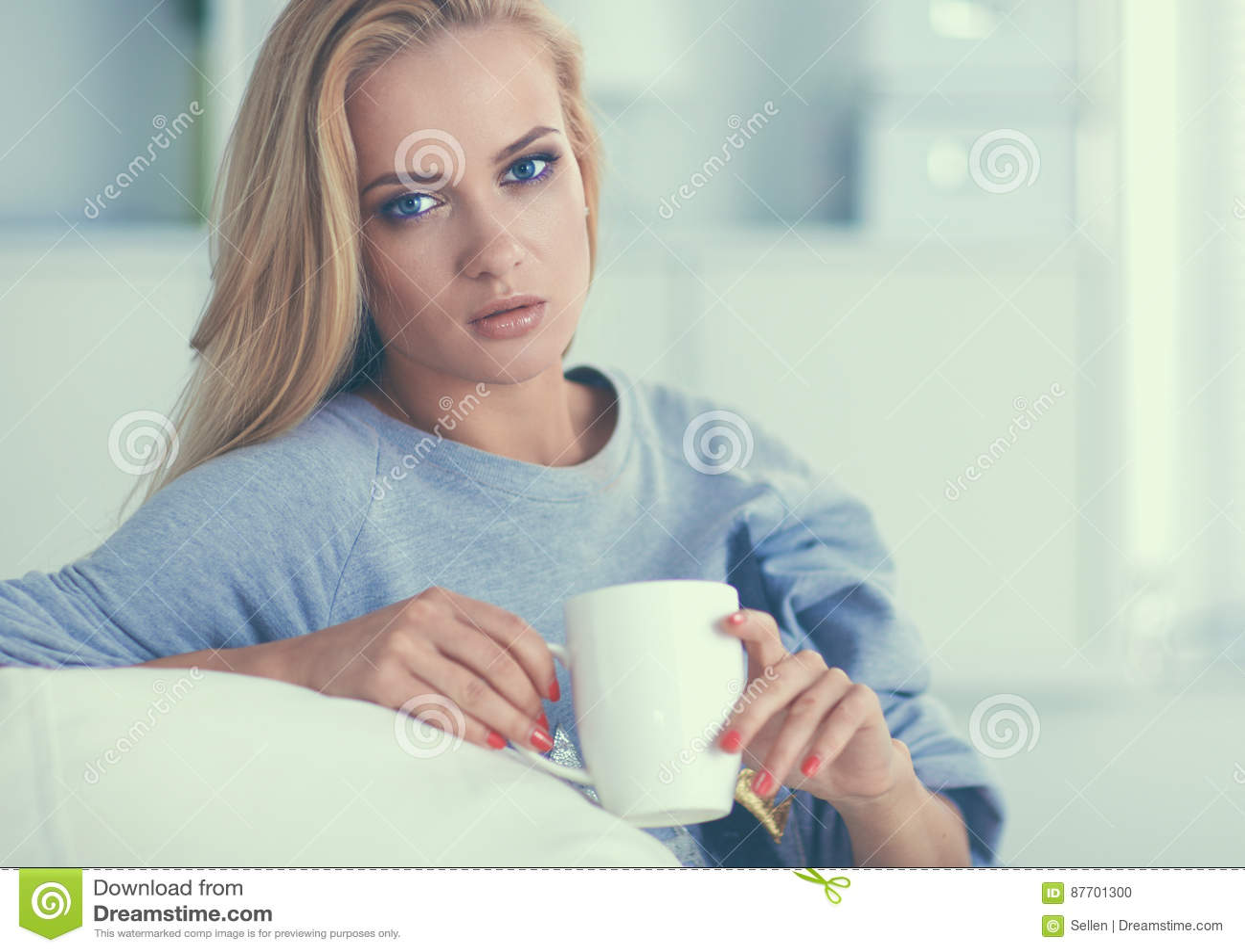 Femme s asseyant sur le divan avec la tasse dans des ses mains
