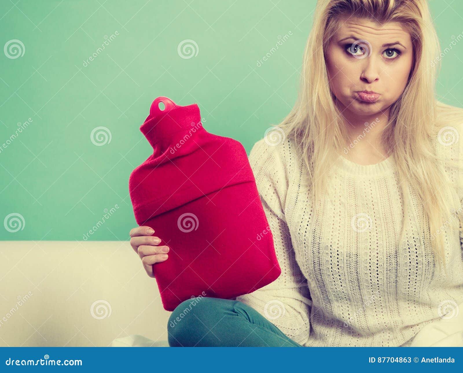 Femme s asseyant sur le divan tenant la bouteille d eau chaude
