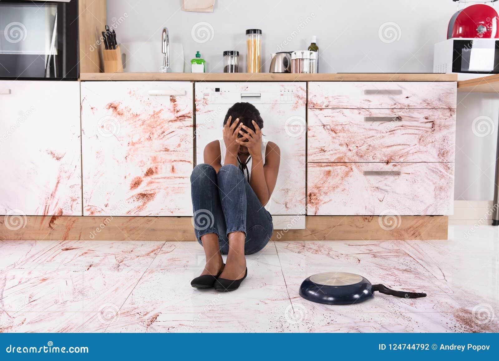 Femme s asseyant sur le plancher de cuisine avec la nourriture renversée