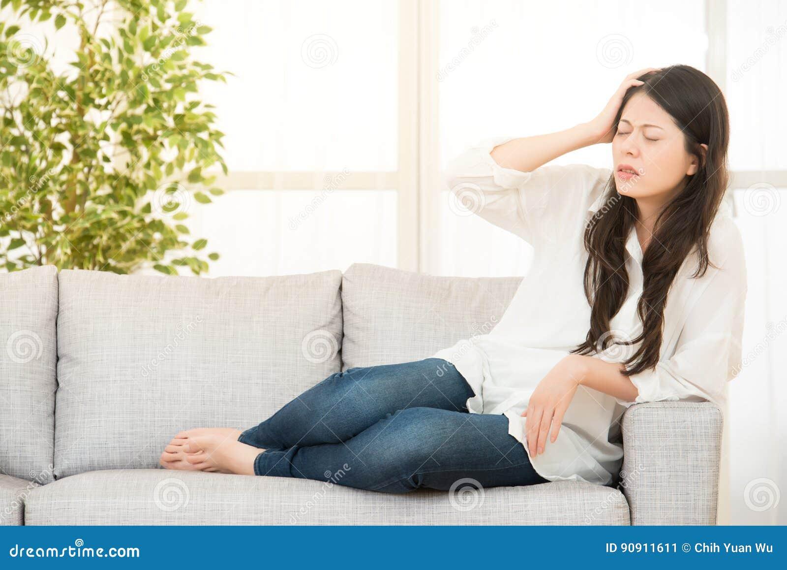 Femme S'asseyant Sur Le Sofa Ayant Le Mal De Tête Image stock ...