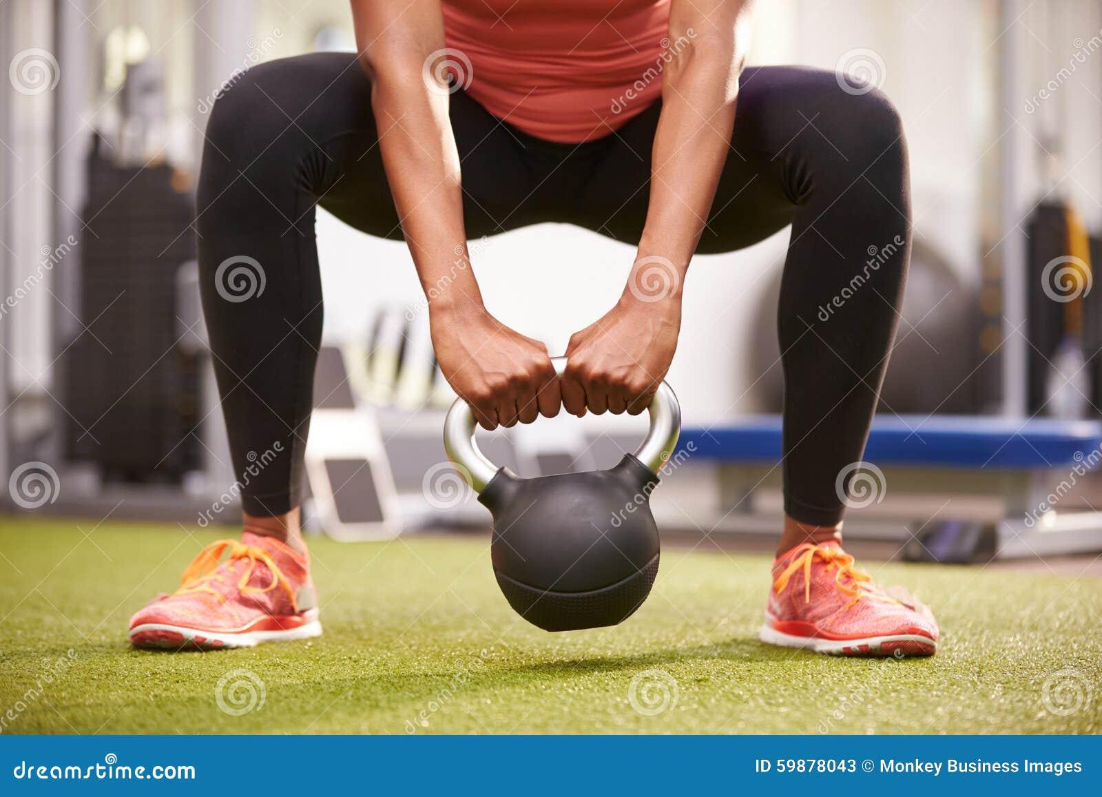 Femme s exerçant avec un poids de kettlebell, culture de bas-section de vue de face