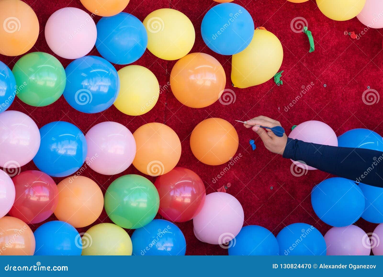 Femme sautant les ballons colorés avec un dard