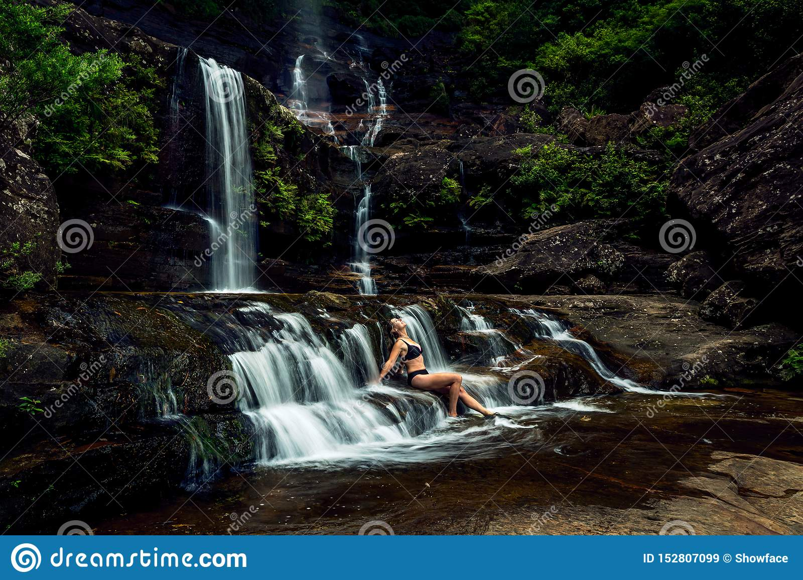 Femme se dorant en cascade luxuriante de montagne