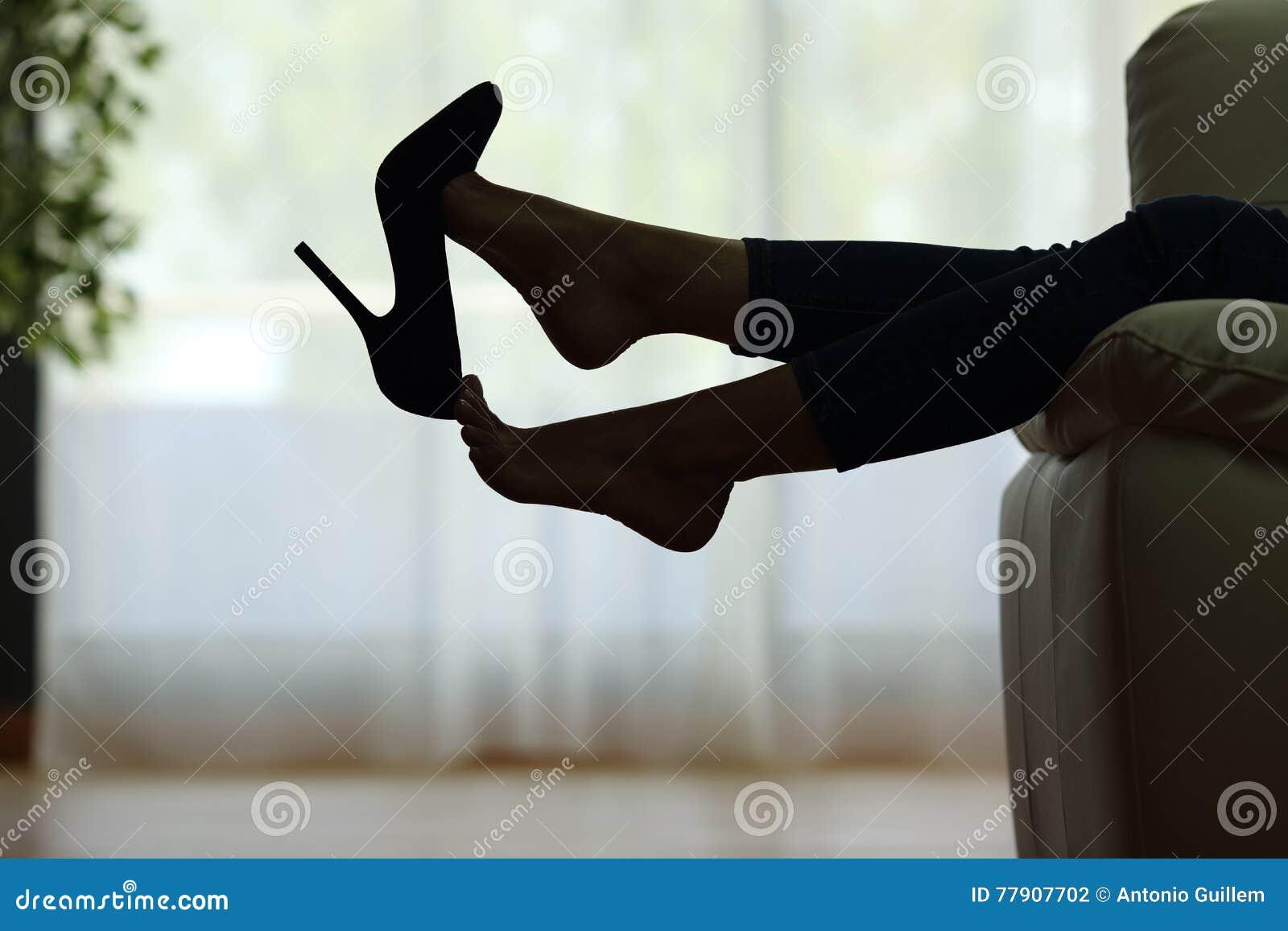Femme se reposant avec des pieds enlevant des chaussures