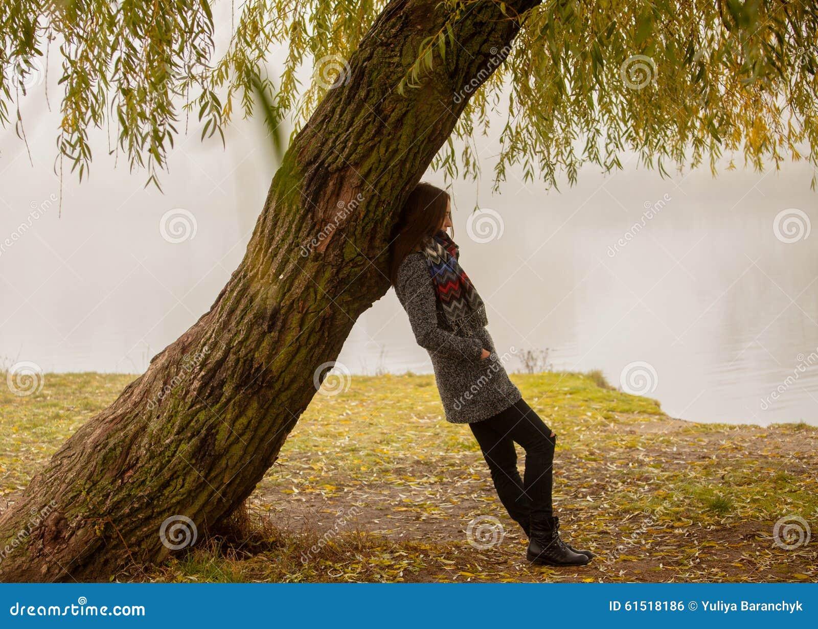 femme seule ayant le repos sous l 39 arbre pr s de l 39 eau dans un jour brumeux d 39 automne photo stock. Black Bedroom Furniture Sets. Home Design Ideas