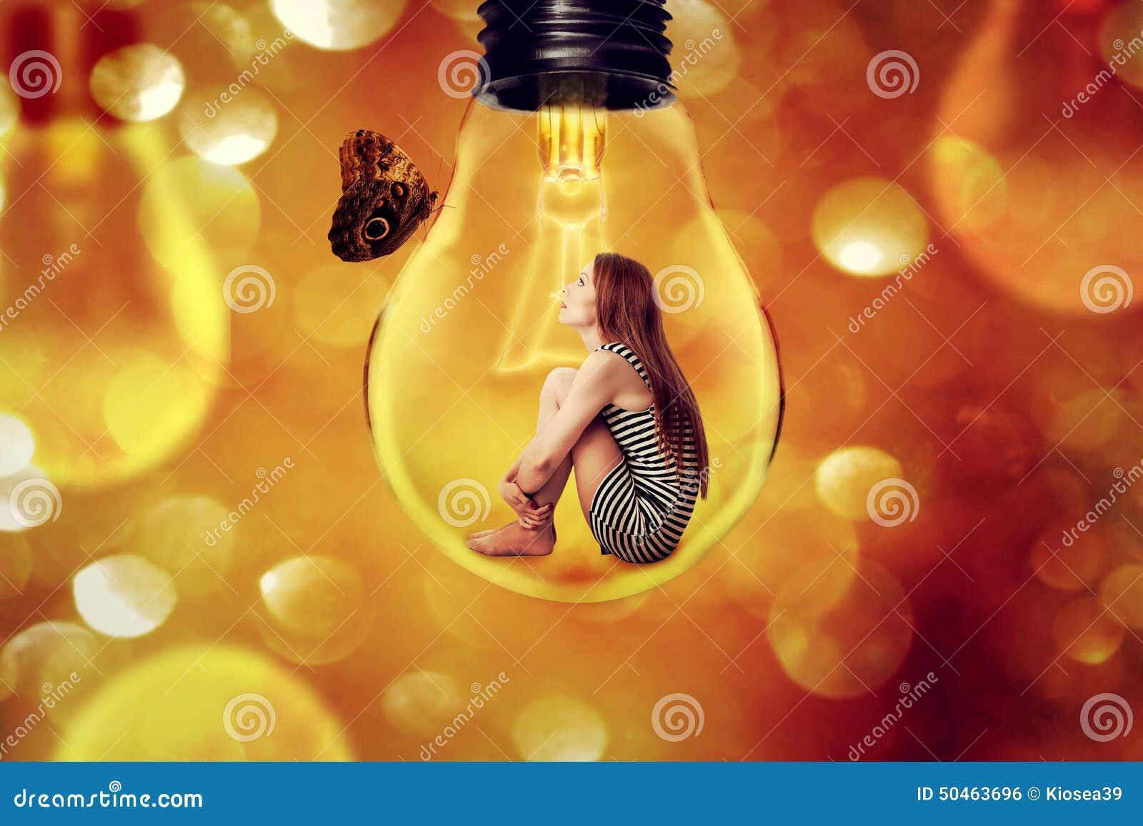 Femme seule s asseyant à l intérieur de l ampoule regardant le papillon