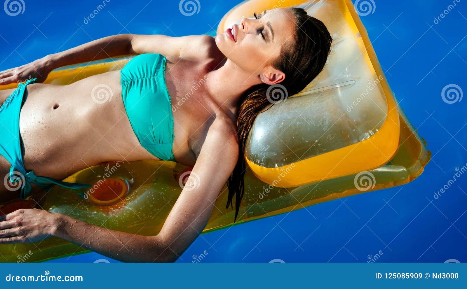 Femme sexy élégante dans le bikini blanc sur le corps mince et bien fait bronzé