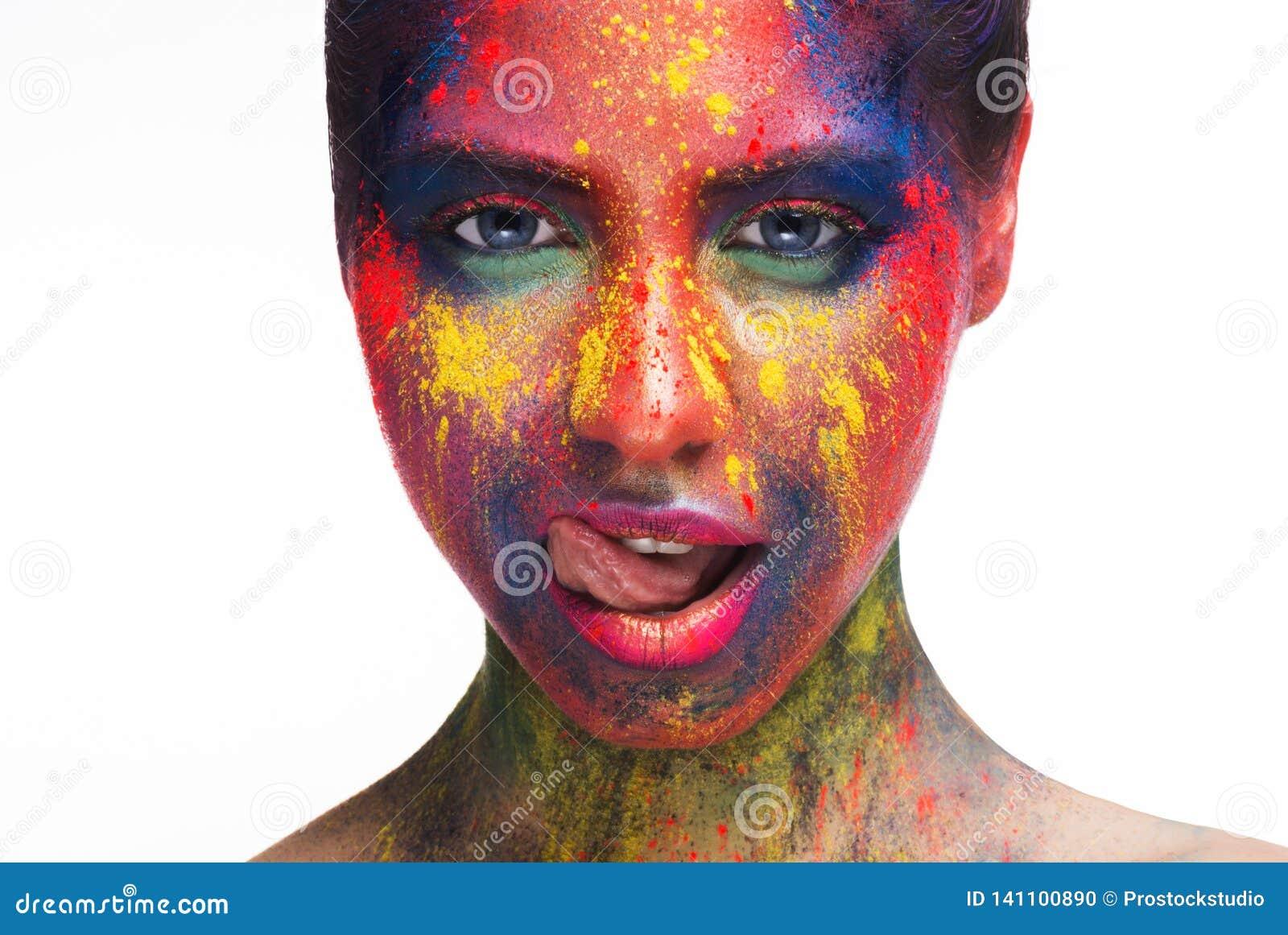 Femme sexy avec le maquillage créatif lumineux léchant ses lèvres