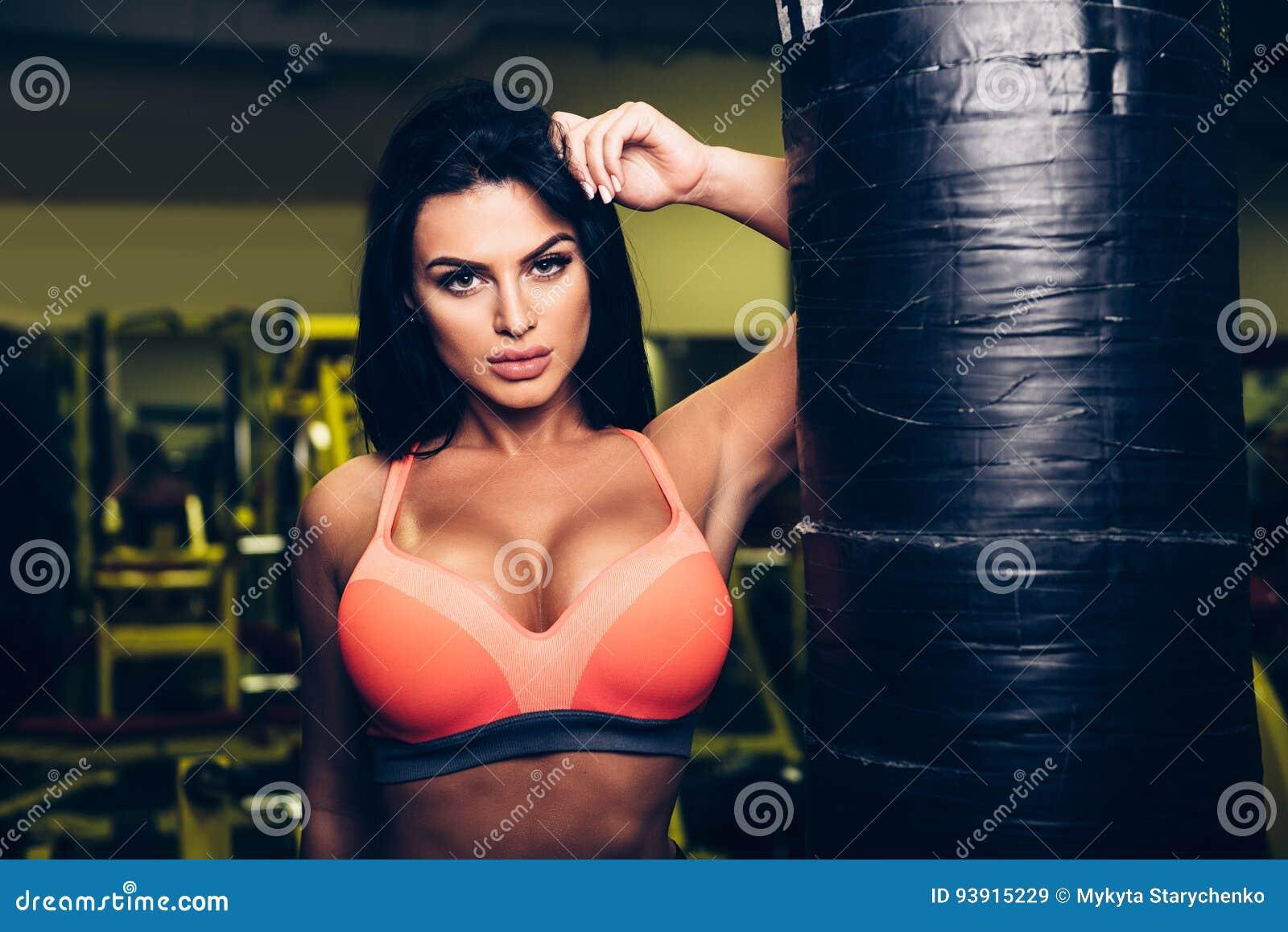 Femme sexy de modèle de forme physique posant près du sac de sable dans le gymnase de sport