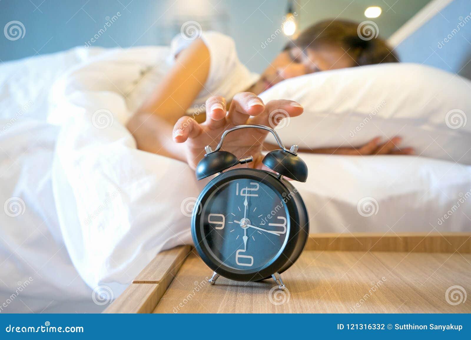 Femme somnolente dans le lit commutant outre du réveil, foyer sélectif