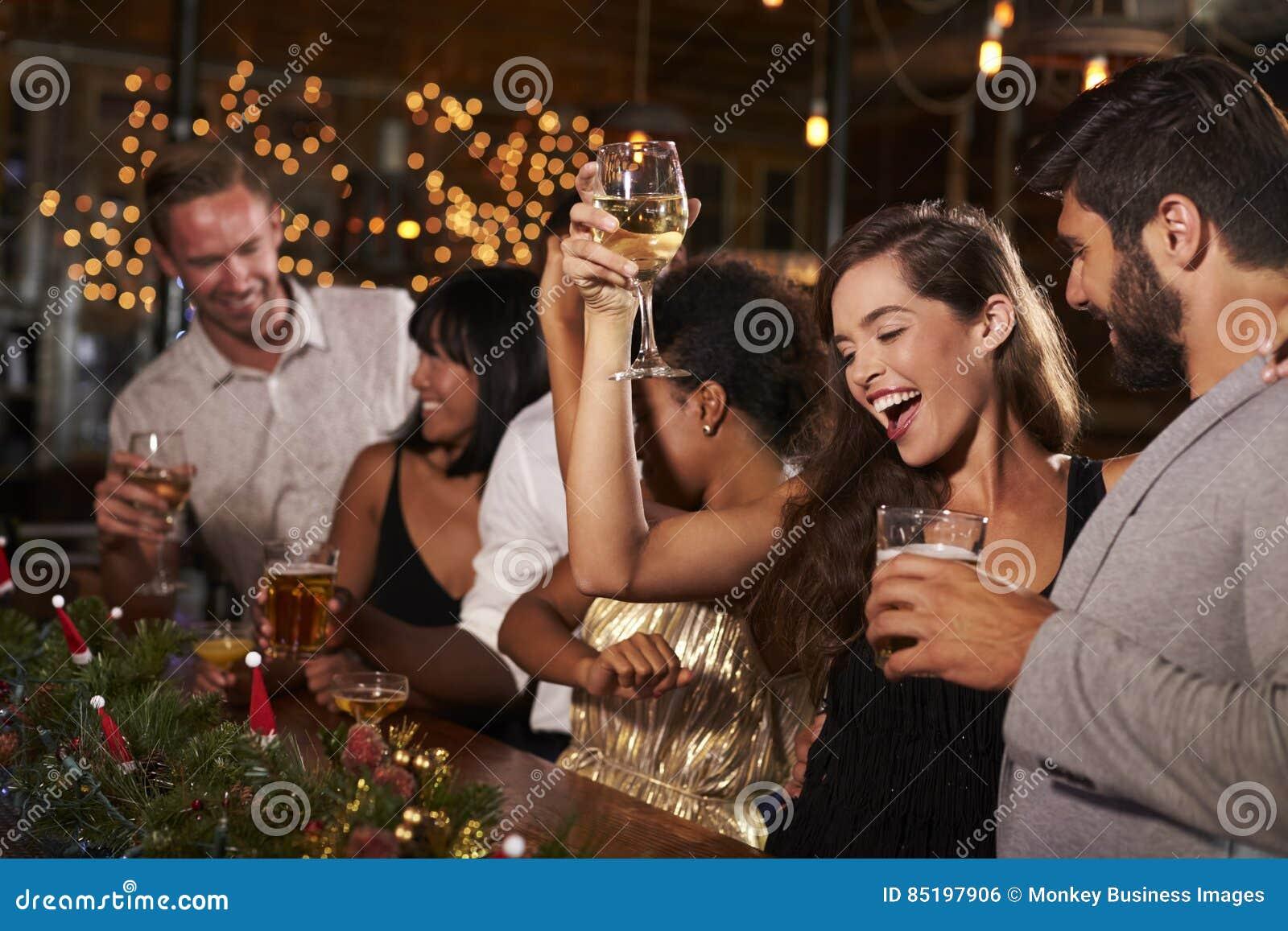 Femme soulevant un verre à une fête de Noël dans une barre