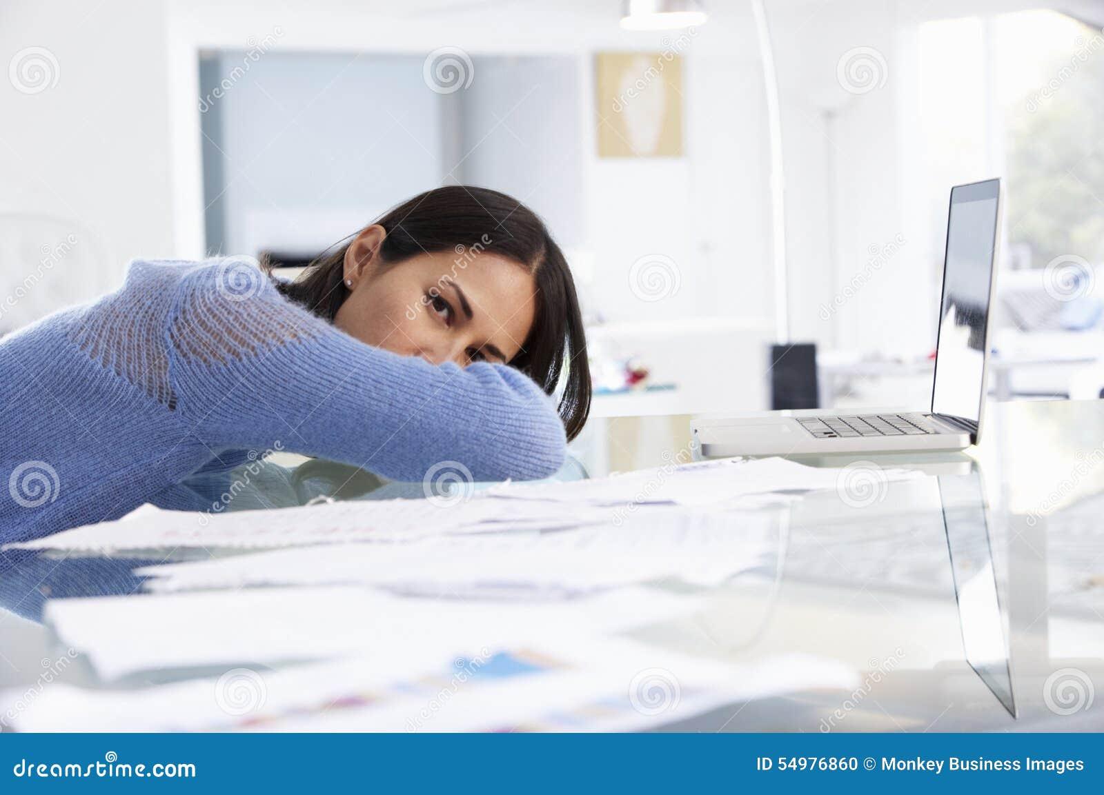 Femme soumise à une contrainte travaillant à l ordinateur portable dans le siège social