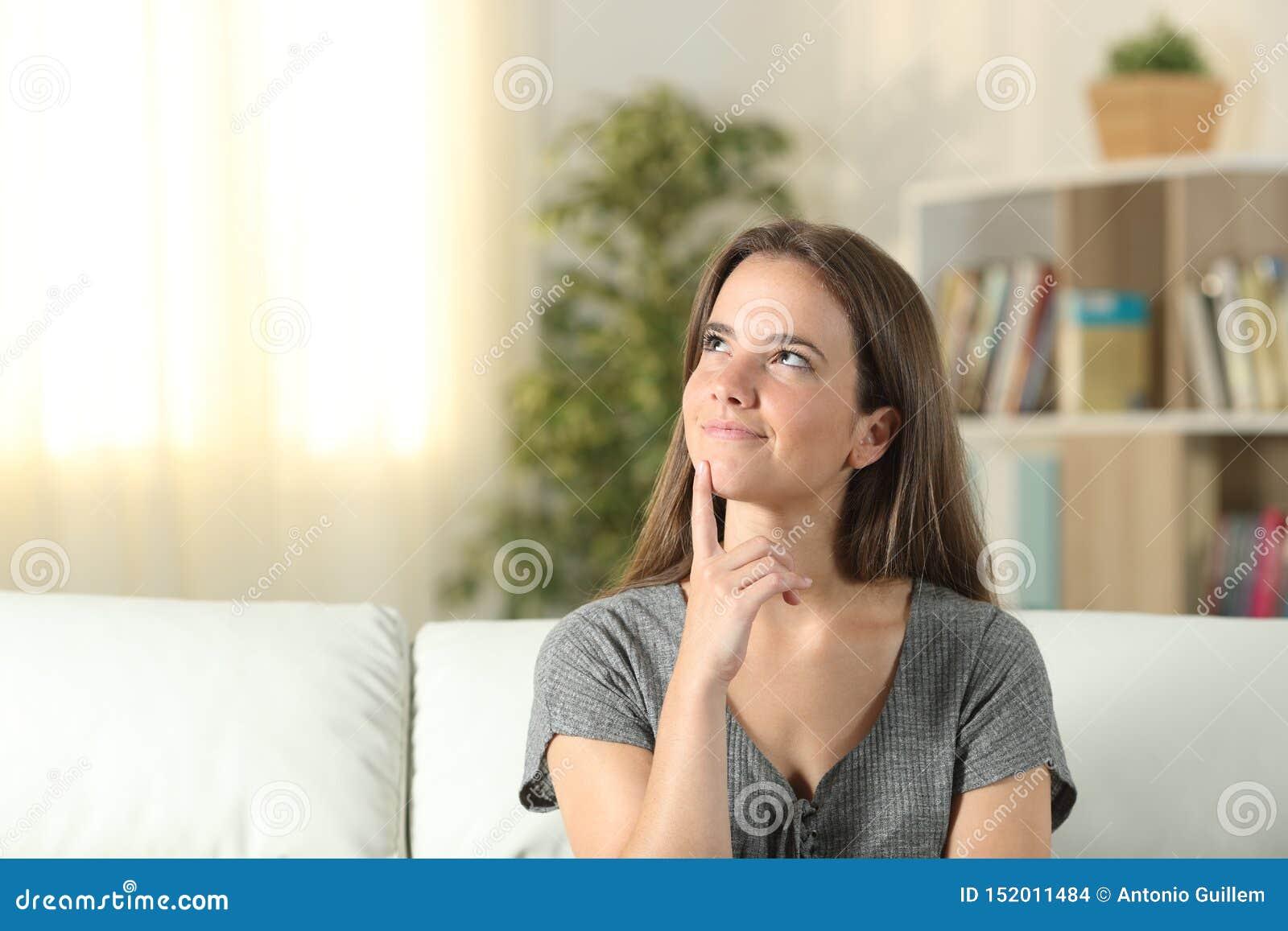 Femme souriante pensant regardant le côté à la maison