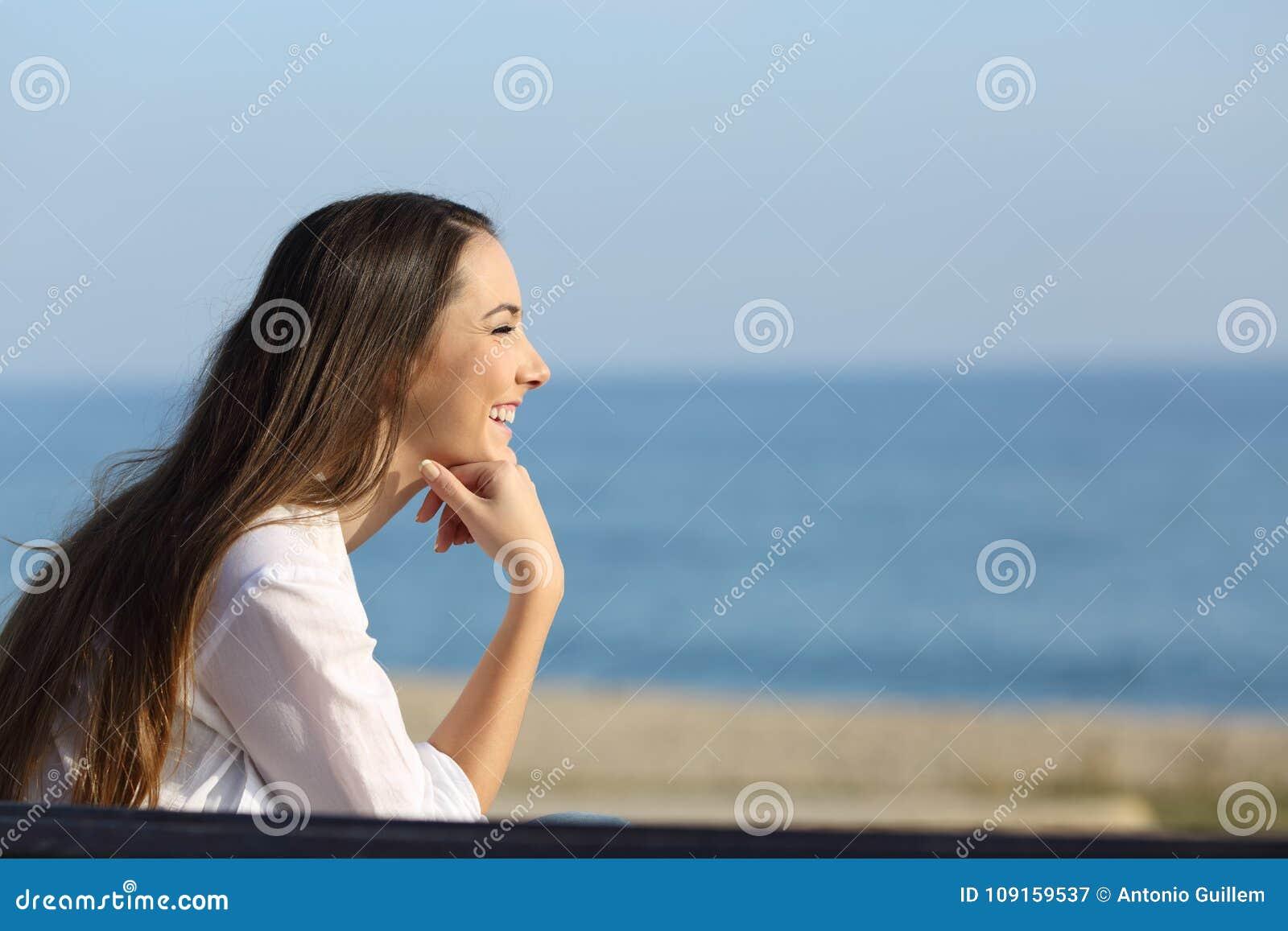 Femme souriante regardant en avant sur la plage