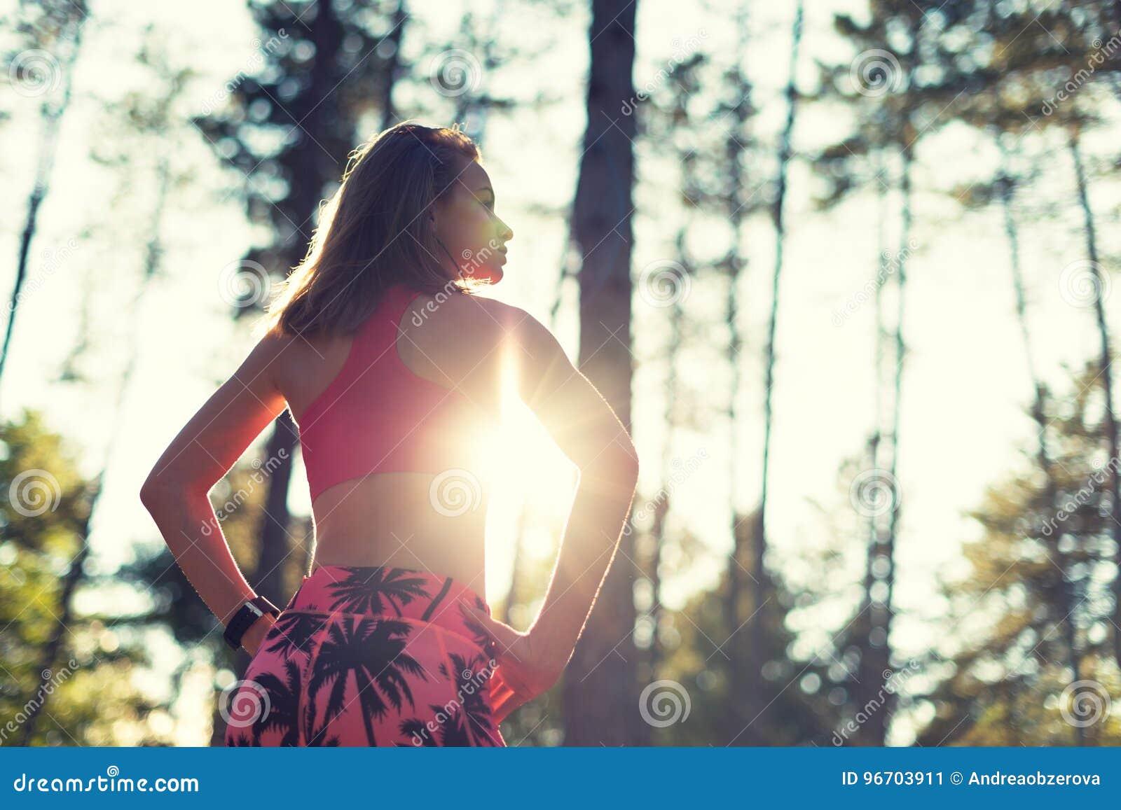 Femme sportive d ajustement attrayant dans une forêt, montre intelligente de port, faisant une pause de séance d entraînement int