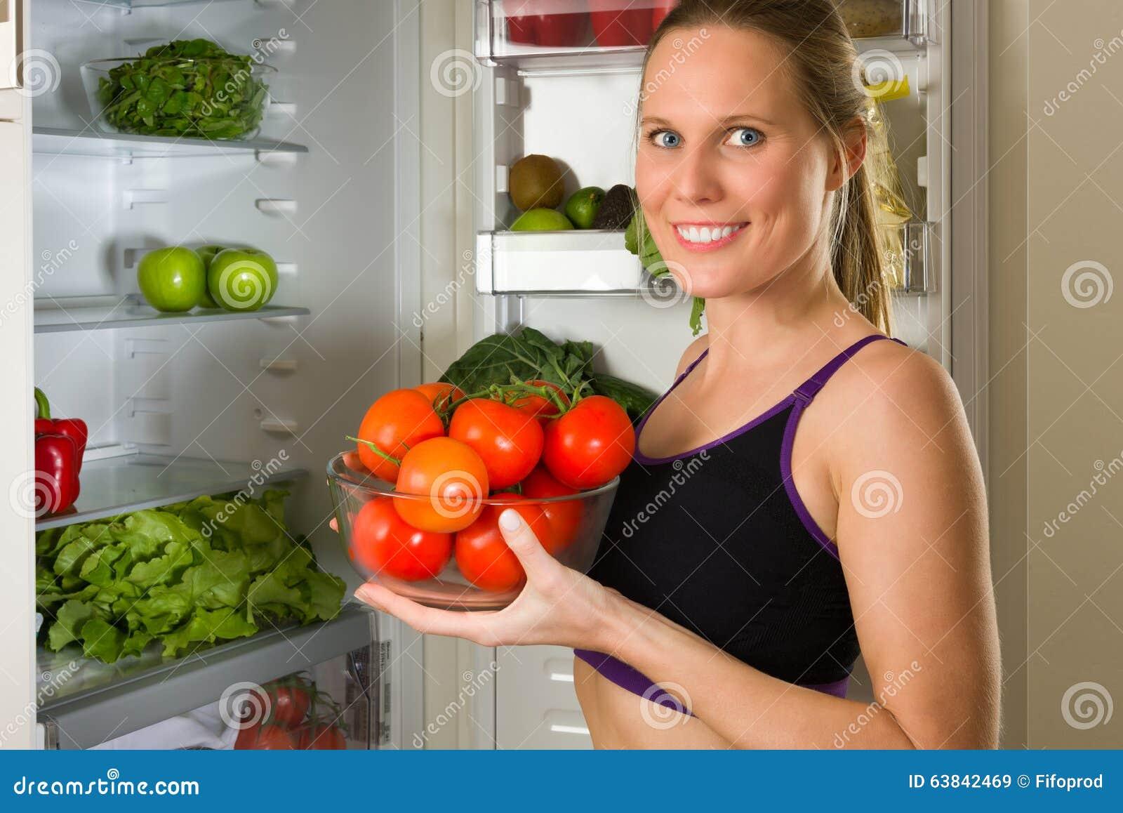 Femme sportive et caucasienne montrant des légumes pour la consommation saine