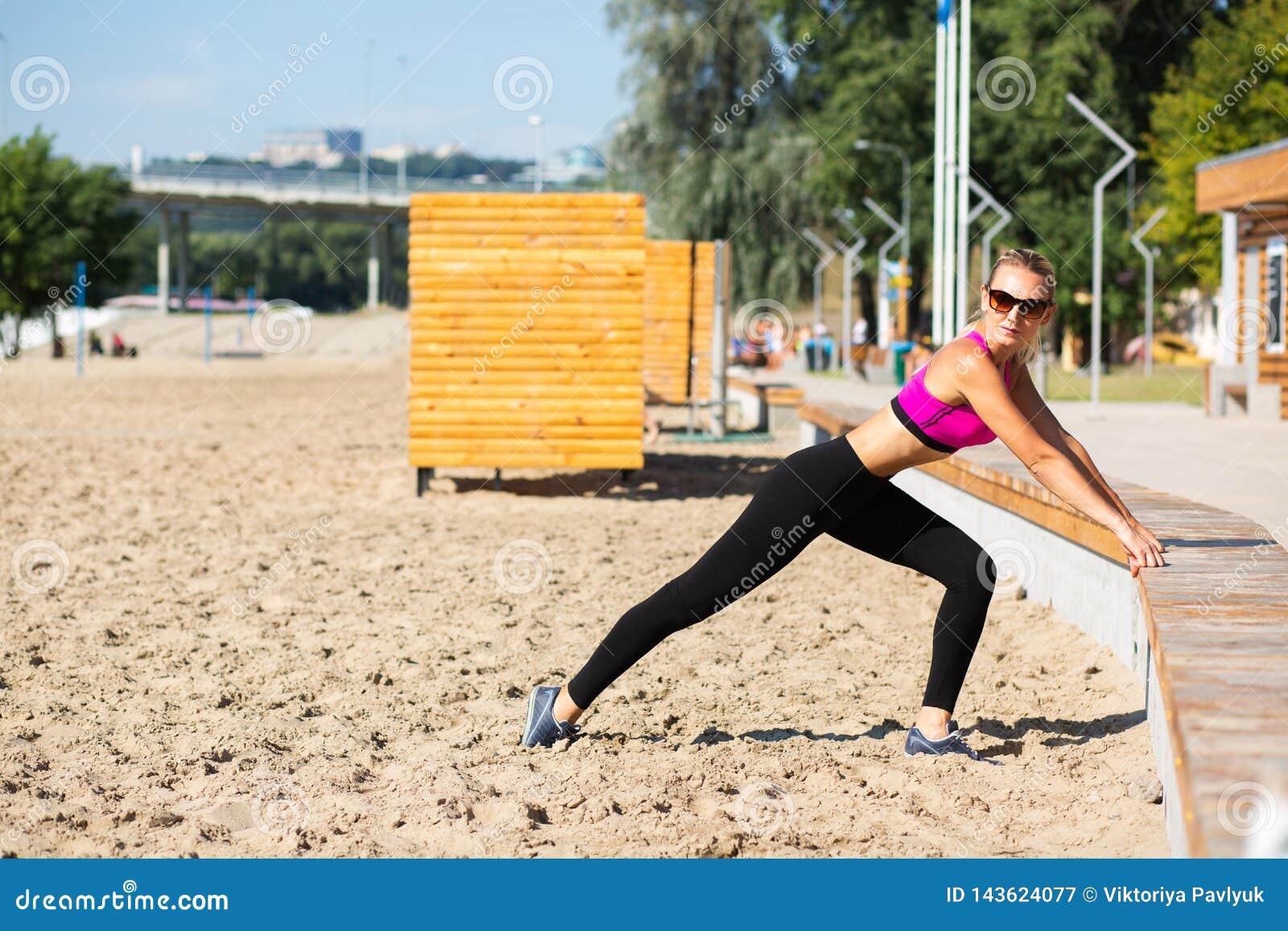 Femme sportive mûre dans des trains de maillot de bain sur la plage
