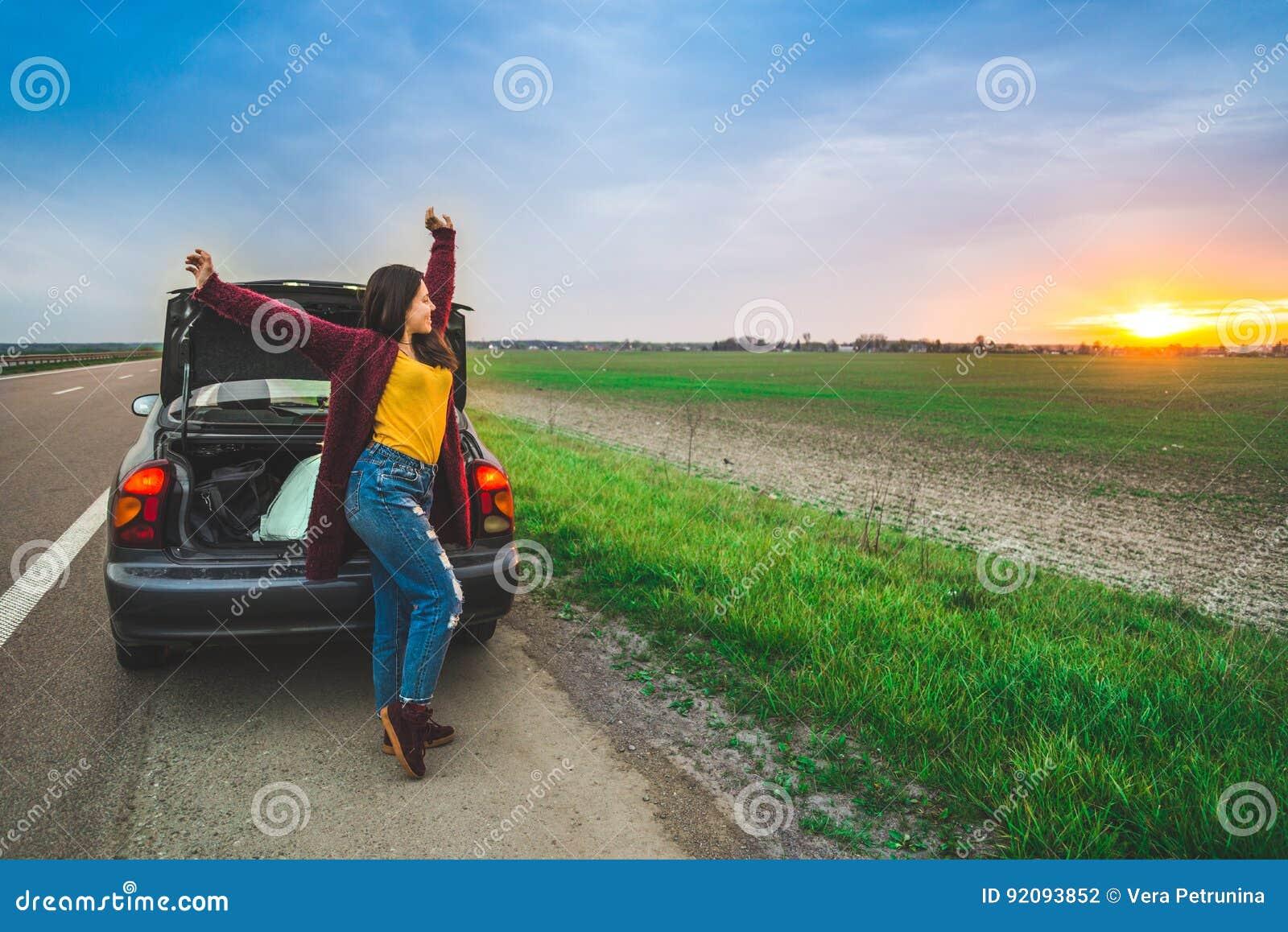 Femme stratching près du long voyage de voiture de voiture